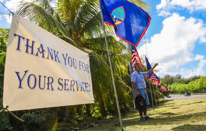 "U.S. Navy veteran Vicente Angoco waves to a passing motorist after he and an assistant posted American and Guam flags along Route 2 in Santa Rita on Monday, Nov. 6, 2017. Angoco says he has erected the display of flags annually for the last 45 years, since he retired from the Navy after serving 20 years. Angoco wanted to show his continuing appreciation to all veterans, retired and active, as well as current military members for their service to their country. ""It's an honor, for me and for all my fellow veterans,"" he said. Saturday is Veterans Day, but Friday is a local and federal holiday."