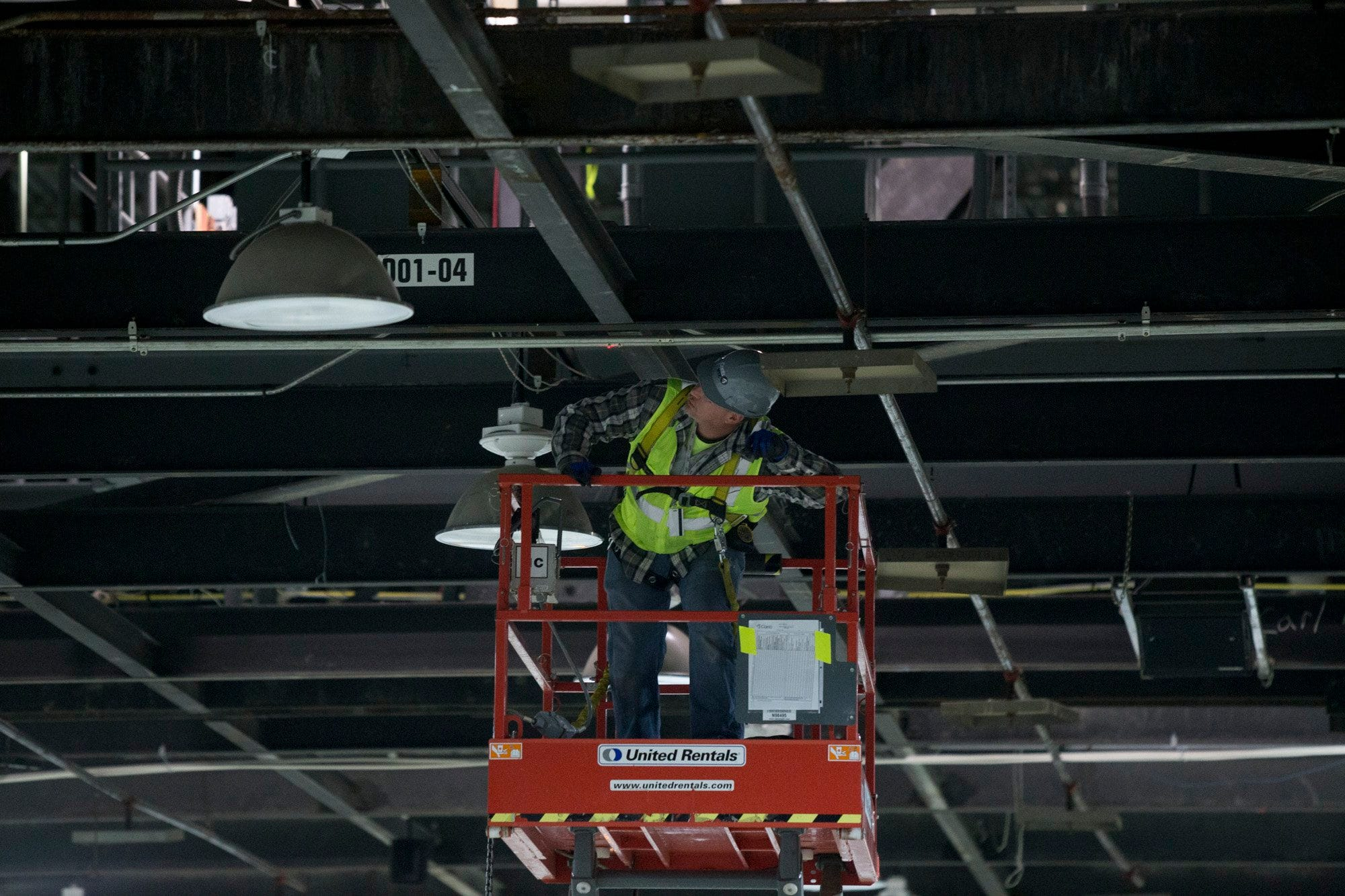A member of a construction crew helps prepare lights