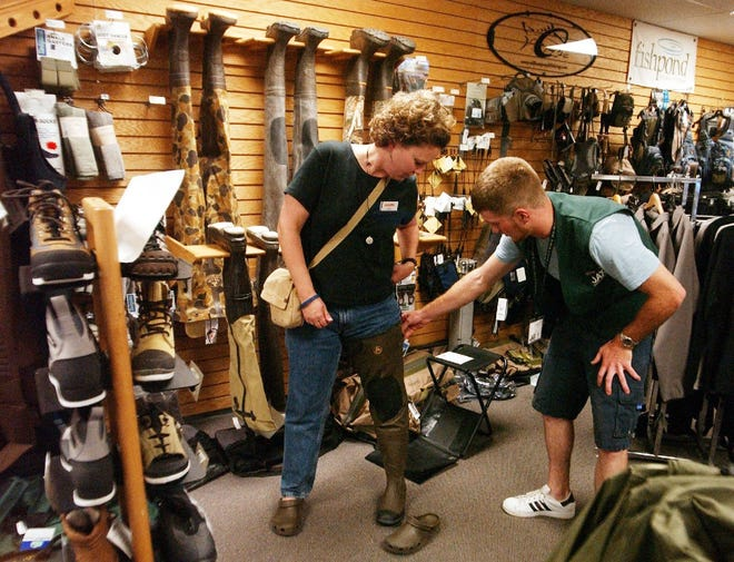 Shelly Whipple tries on a pair of hip waders at Jax Outdoor Gear.
