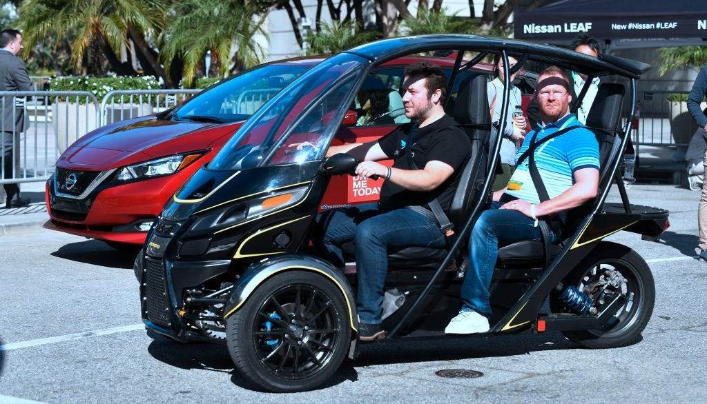 People take a ride on the electric Arcimoto, a three-wheel