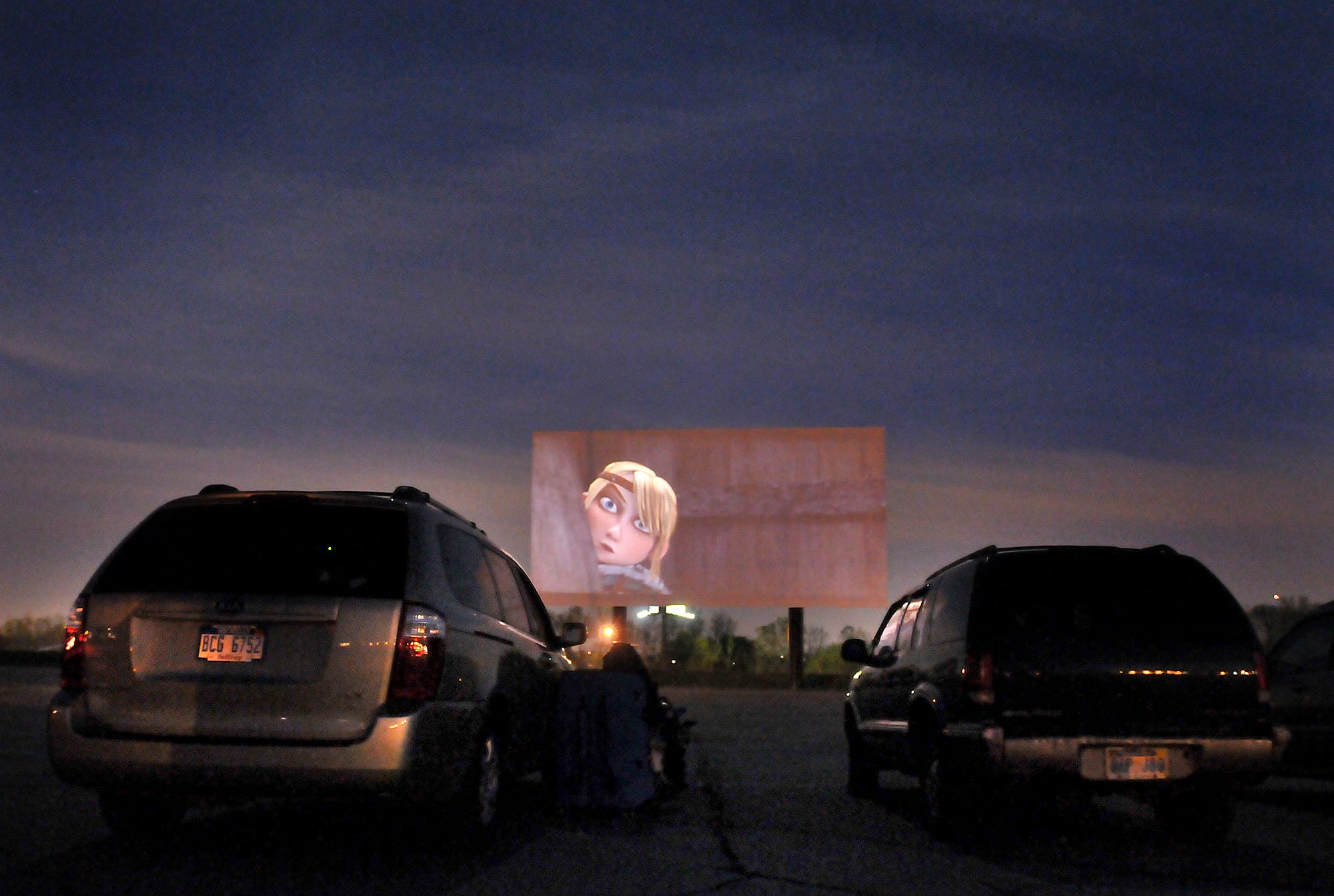 Moviegoers sit in their vehicles and watch the movie