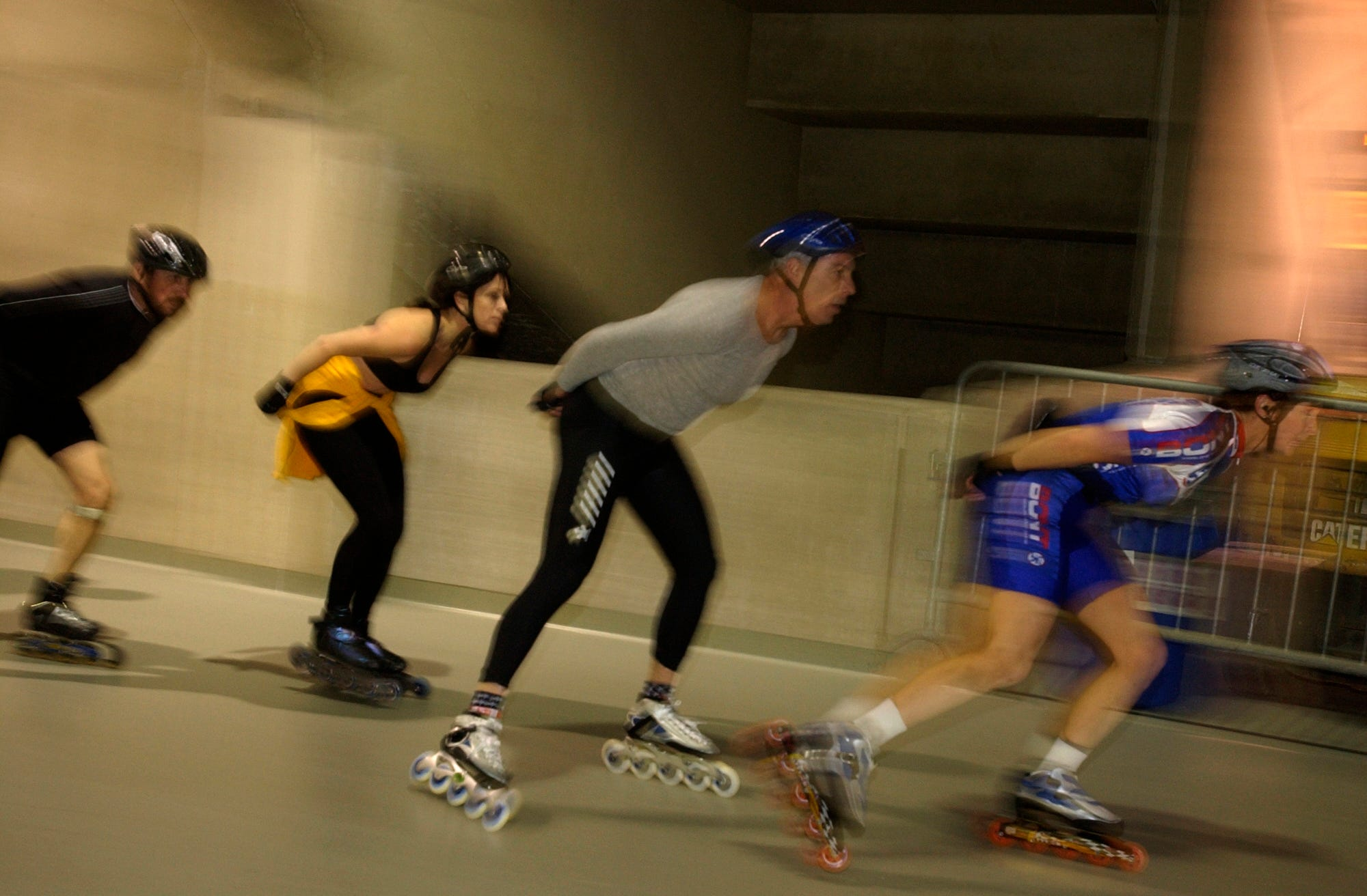 A line of speed skaters skirts the inside wall during