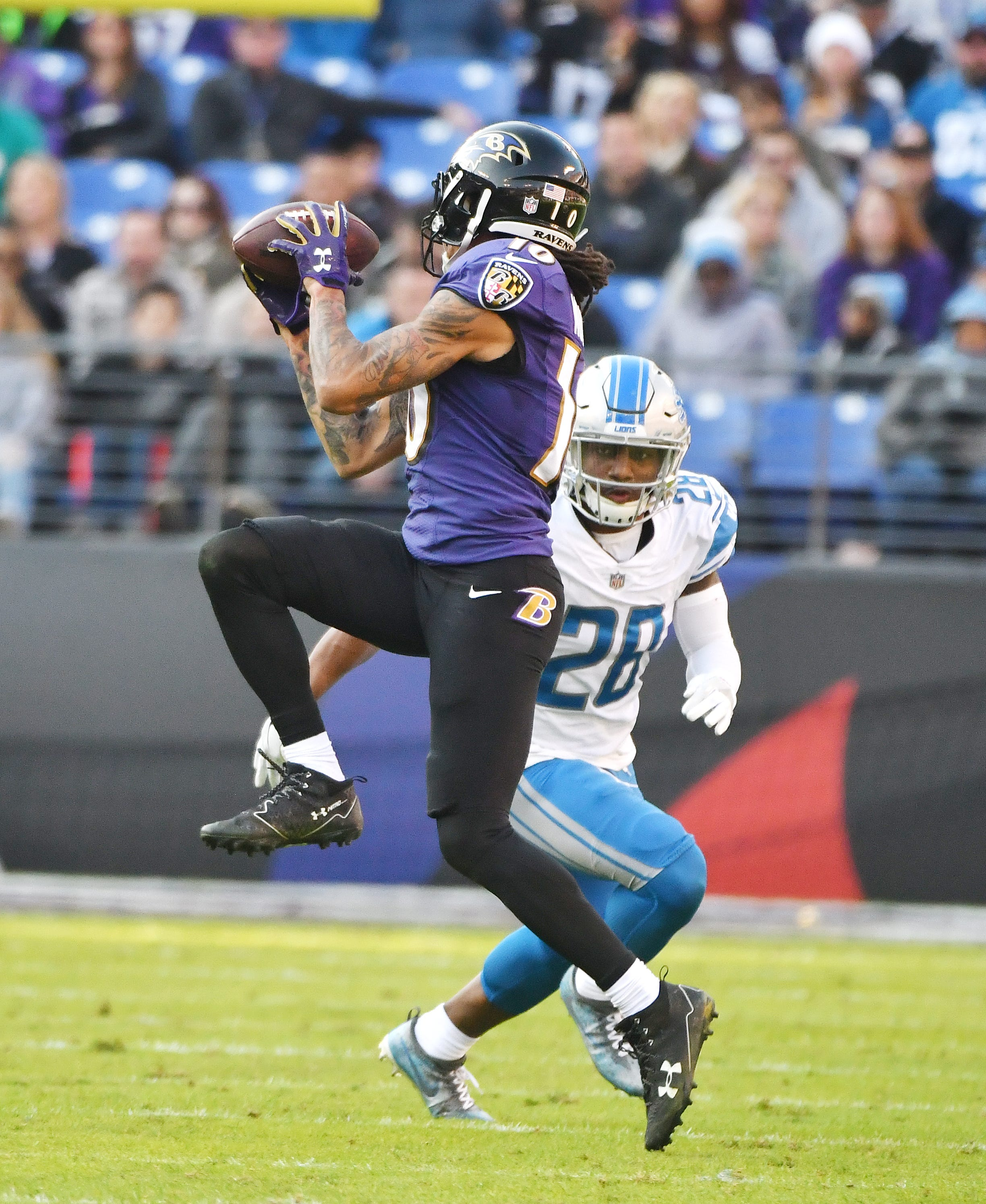 Ravens' Chris Moore makes a reception in front of Lions'