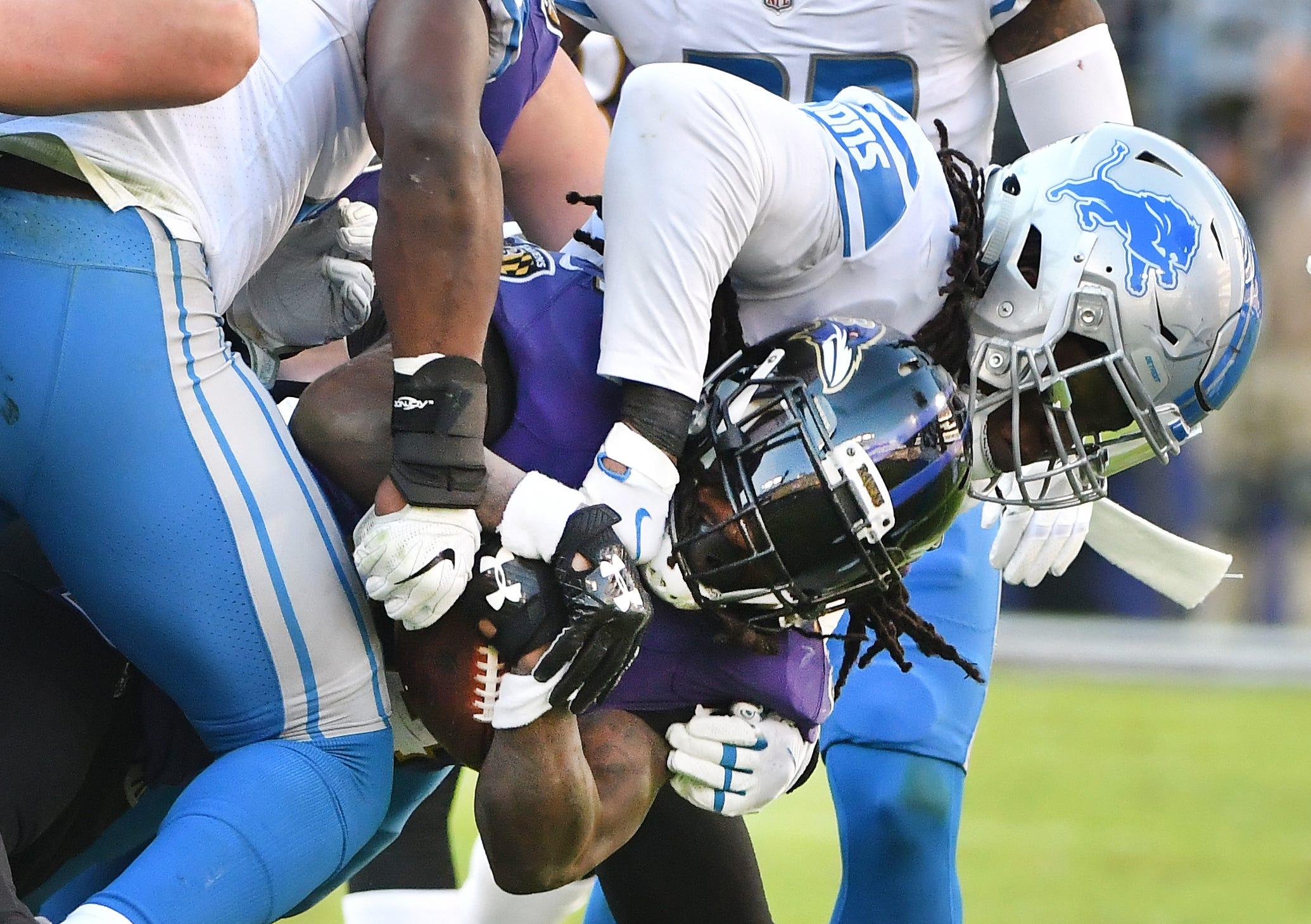 Lions' Ezekiel Ansah brings down Ravens running back