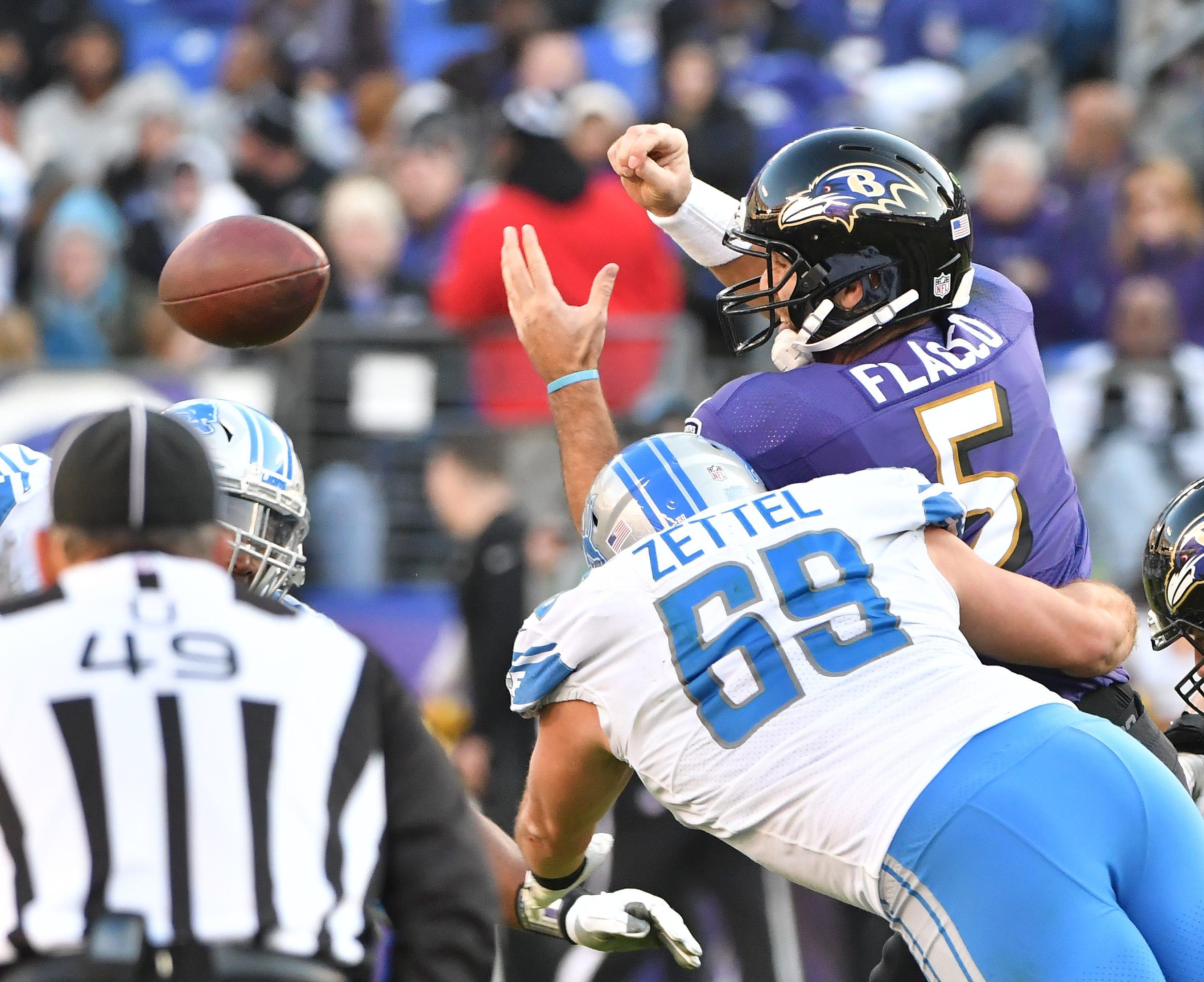 Lions' Anthony Zettel hits Ravens quarterback Joe Flacco,