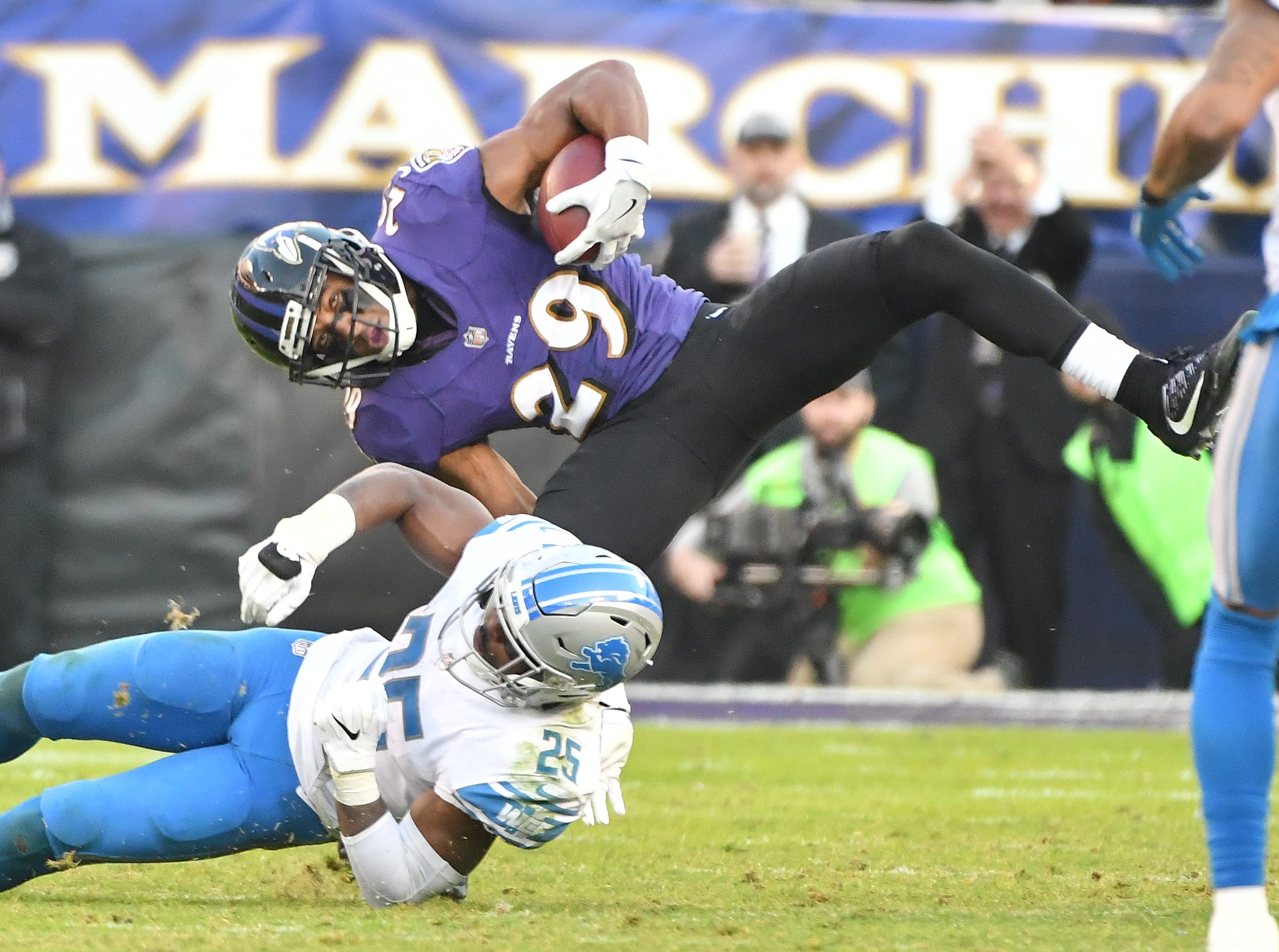 Ravens' Marlon Humphrey is flipped by Lions' Theo Riddick