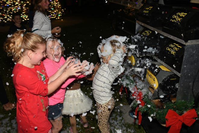 Amelia Skender and Addison Heinrich, both 8, enjoy the snow machine. The Christmas Island Style tree-lighting ceremony at Veterans' Community Park drew its biggest crowd ever.