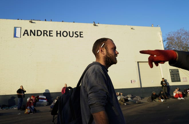 Homeless men and women wait in line outside Andre House for a free meal prepared by volunteers.