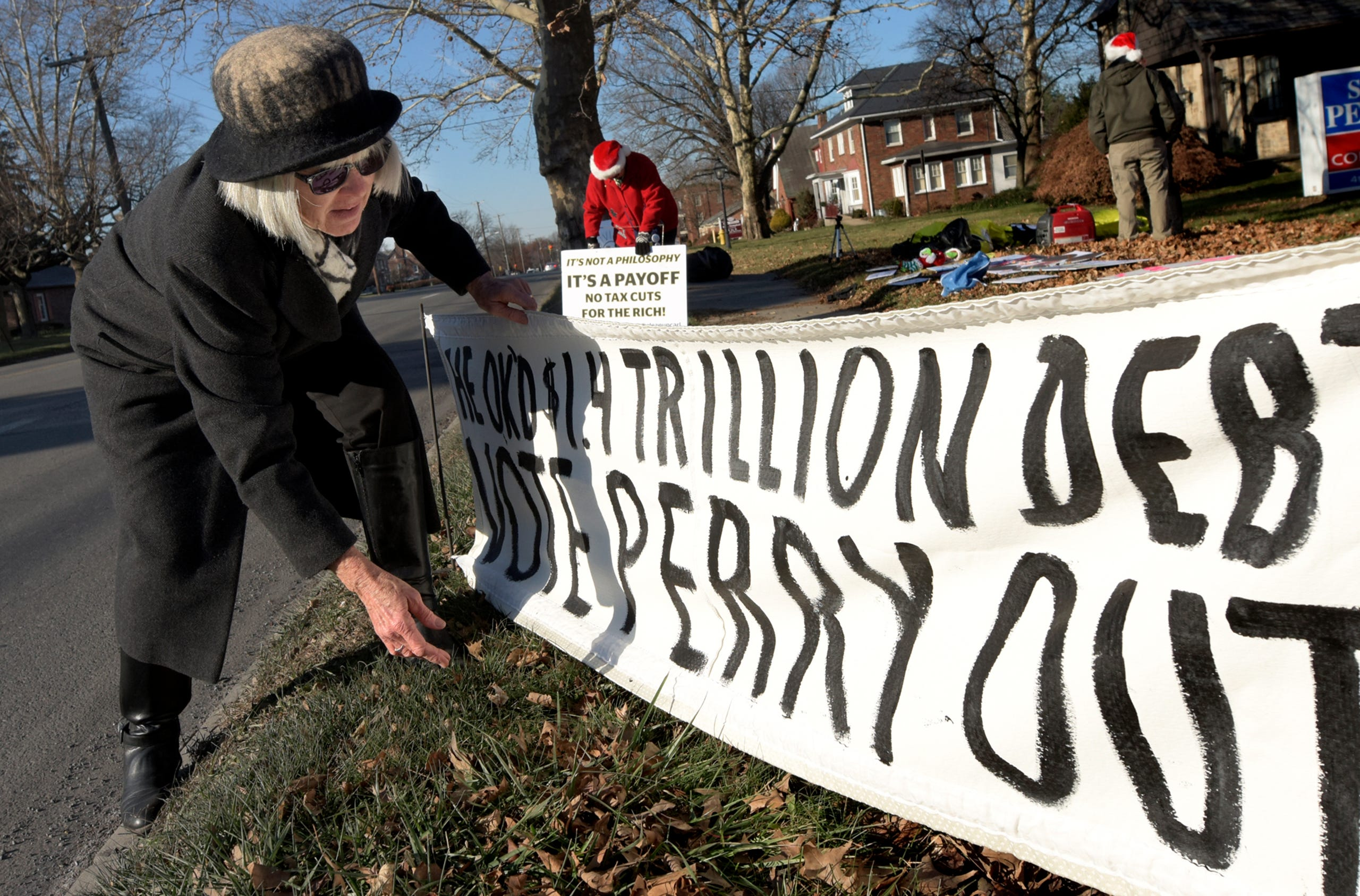 Indivisible York members Mary Barnes of Springfield Township straightens a banner while Nikki Byer of Newberry Township plants a sign, background, while preparing for a