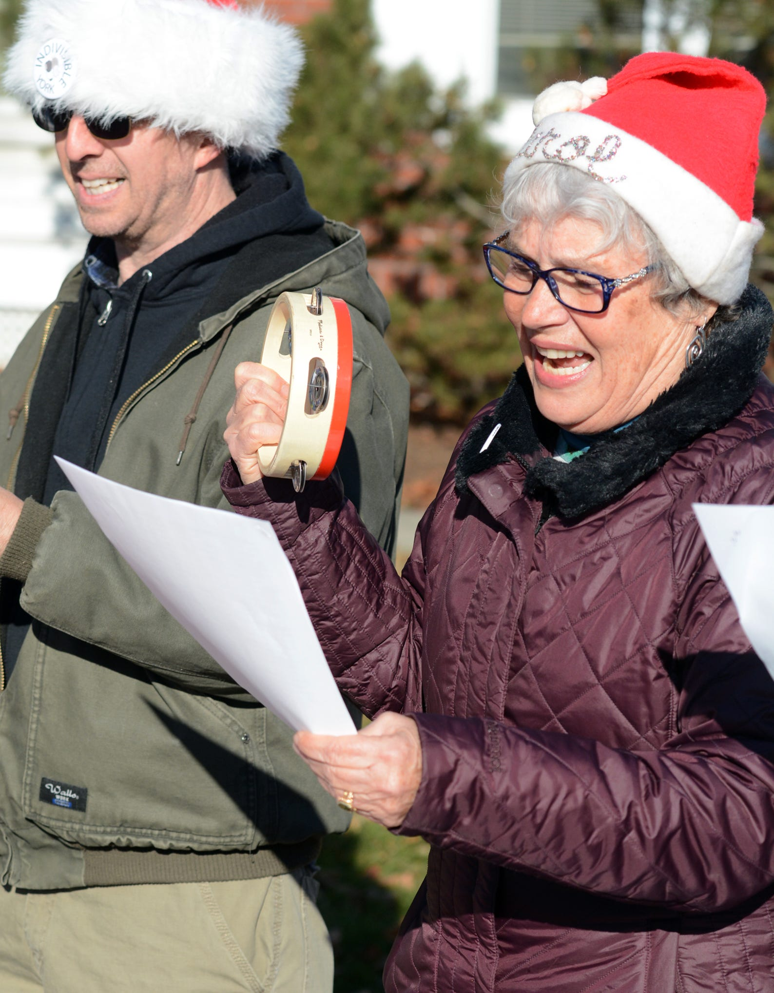 Indivisible York member Carol Stowell of Thomasville plays tambourine and sings during a