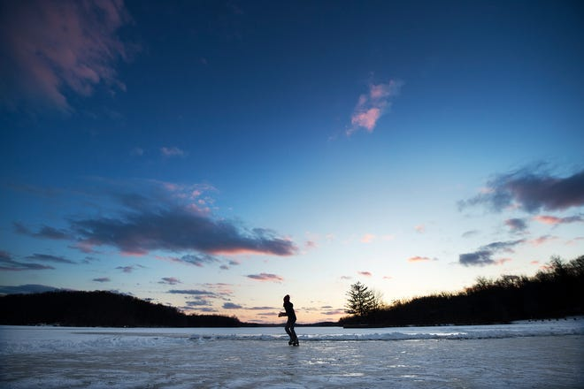 Elizabeth Herb skates beneath a setting sun at Gifford Pinchot State Park, where the average ice depth is 4 inches. Elizabeth, from Camp Hill, was visiting the lake with her brother and parents. As the bitter cold continues, ice is thickening on area lakes. People are warned to take precautions, however, before heading out on the ice on January 1, 2018.
