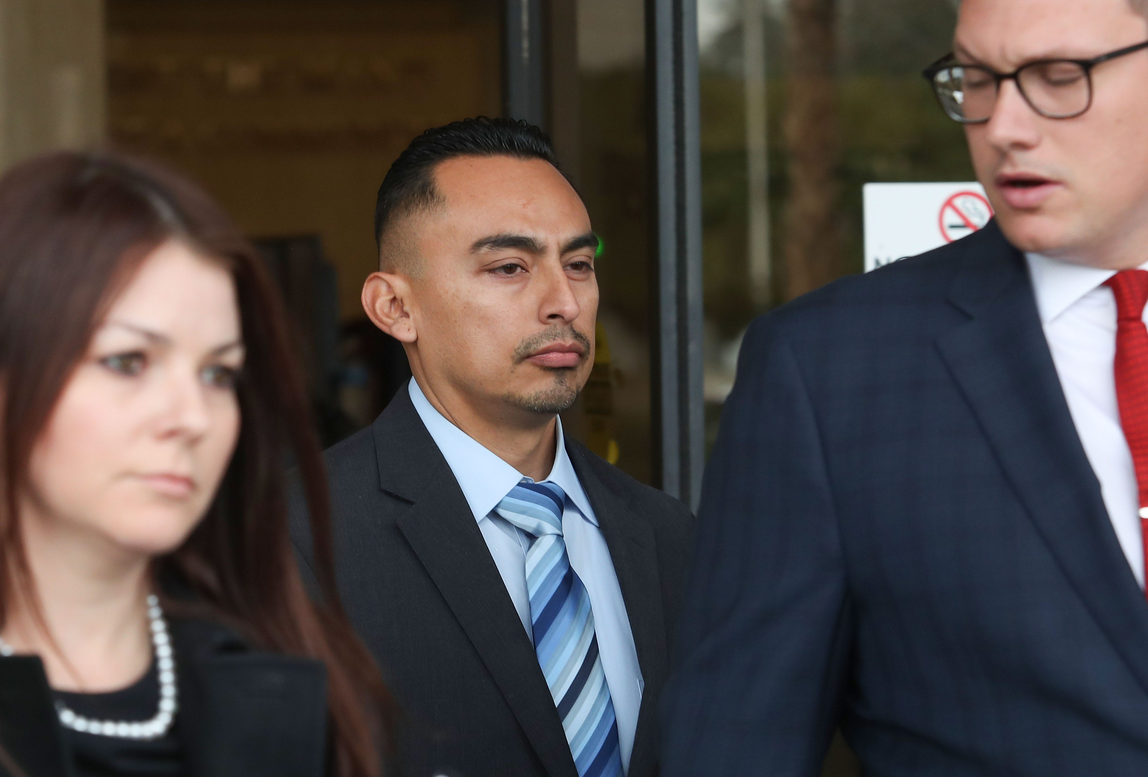 Former Riverside County Sheriff's Deputy Oscar Rodriguez, center, walks out of the Larson Justice Department in Indio, Jan. 3, 2018. Rodriguez has been charged with murder.