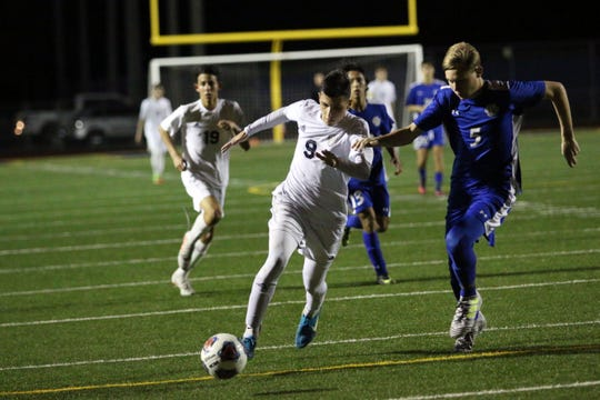 Naples striker Luis Baldivieso (9) dribbles up the field during the Golden Eagles' match with Barron Collier at Staver Field on Thursday. With a 3-0 win over Barron Collier, the Eagles secured the top seed in the district with an undefeated record of 6-0-2.