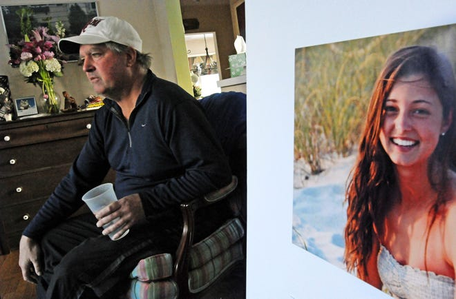 In this Jan. 23, 2014 file photo, James Holleran, father of Madison Holleran, a University of Pennsylvania freshman who took her own life, talks about his daughter while sitting next to a favorite photo of her at his home in Allendale, N.J. Nearly half of the largest U.S. public universities do not track suicides among their students, despite making investments in prevention at a time of surging demand for mental health services. After her 2014 suicide, one of her former teachers in New Jersey was surprised to learn learn many universities don't report suicide statistics.