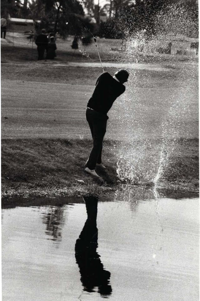 c30a12182 An amateur golfer takes a shot out of the water at the Phoenix Open in 1975