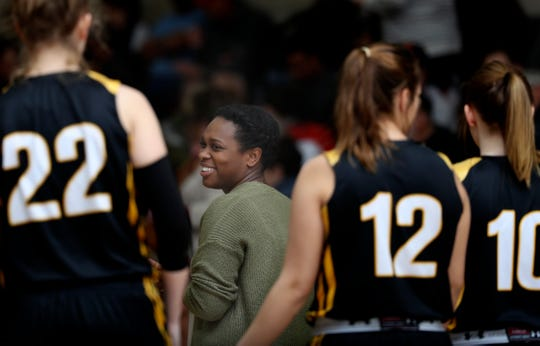 Enterprise assistant girls varsity basketball coach Ravien Lawson, center, talks with team members during a past game at Foothill.