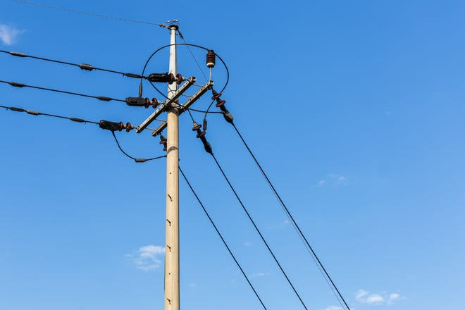 A stock photo of a utility pole and power lines.