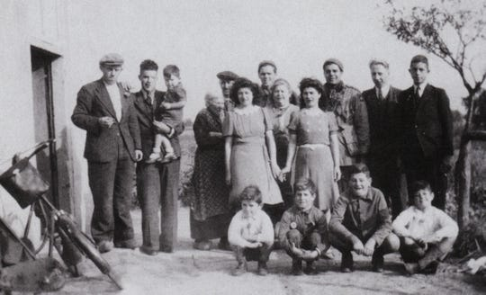 James Megellas, third from right in back row, poses with a Dutch family shortly after the jump into Holland on Sept. 17, 1944.