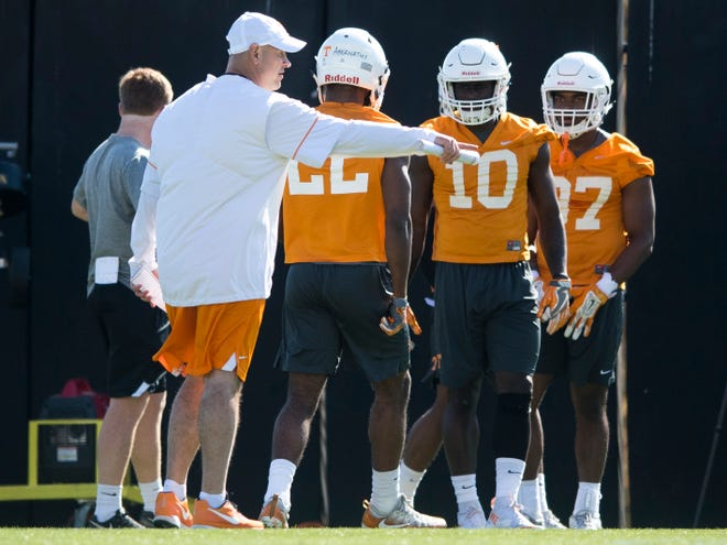 Tennessee coach Jeremy Pruitt works with players at practice Thursday.
