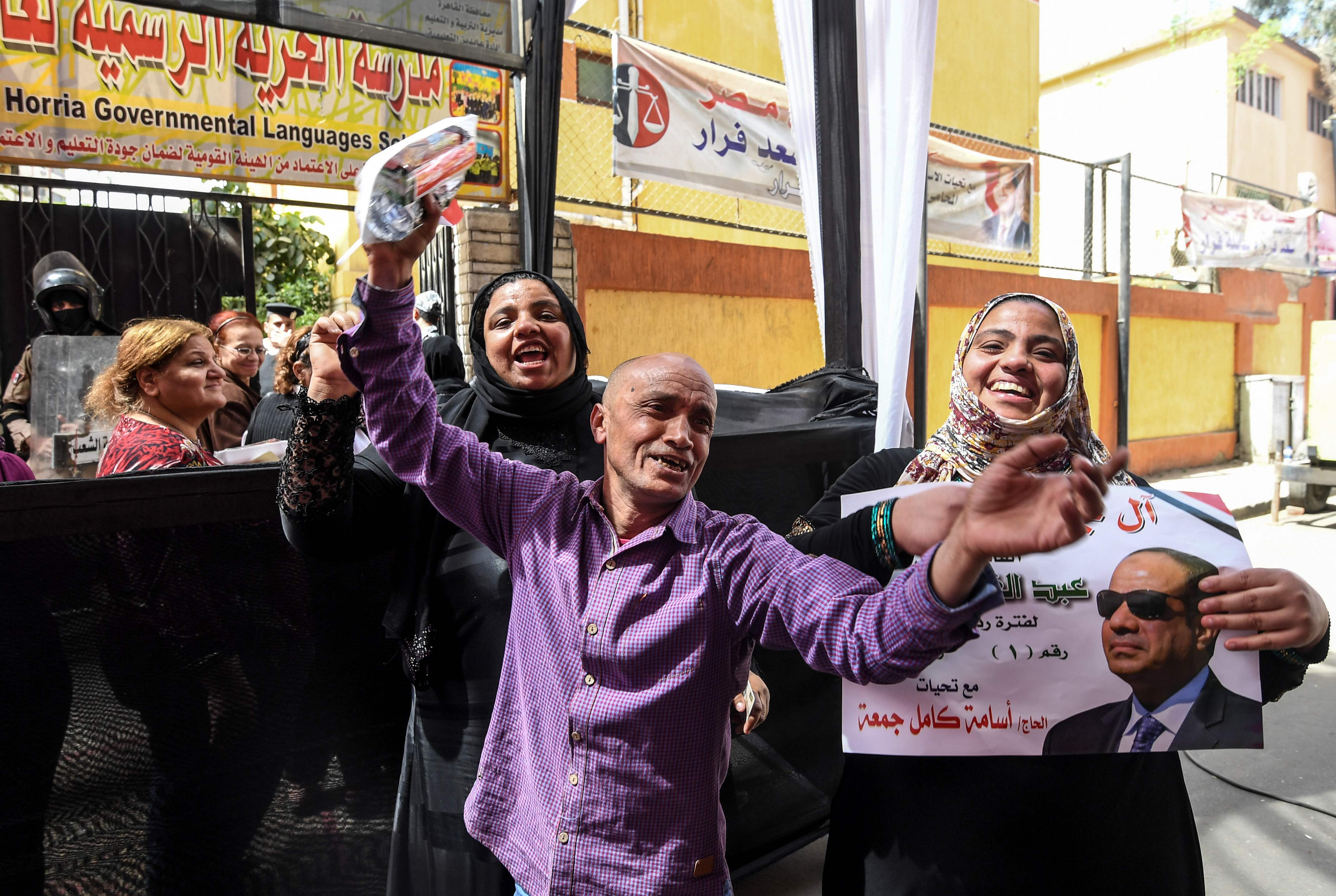 Egyptians dance and celebrate with an electoral poster of incumbent President Abdel Fattah al-Sisi outside a polling station in Cairo on March 26, 2018 on the first day of voting in the 2018 presidential election.  Egyptians head to the polls in a thr
