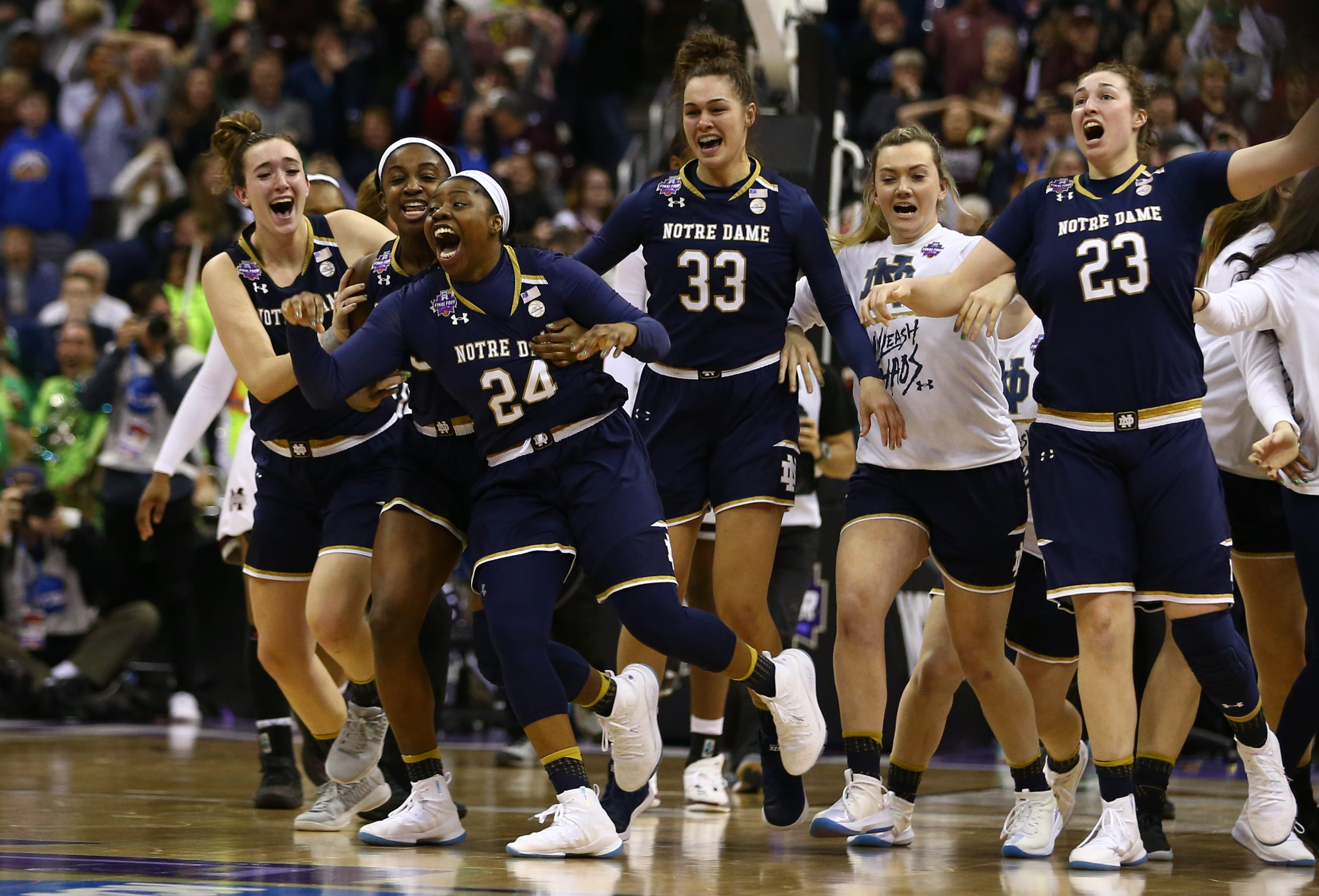 Notre Dame Fighting Irish guard Arike Ogunbowale celebrates with teammates after making the game winning basket against the Mississippi State Lady Bulldogs during the fourth quarter in the championship game of the women's Final Four in the 2018 NCAA