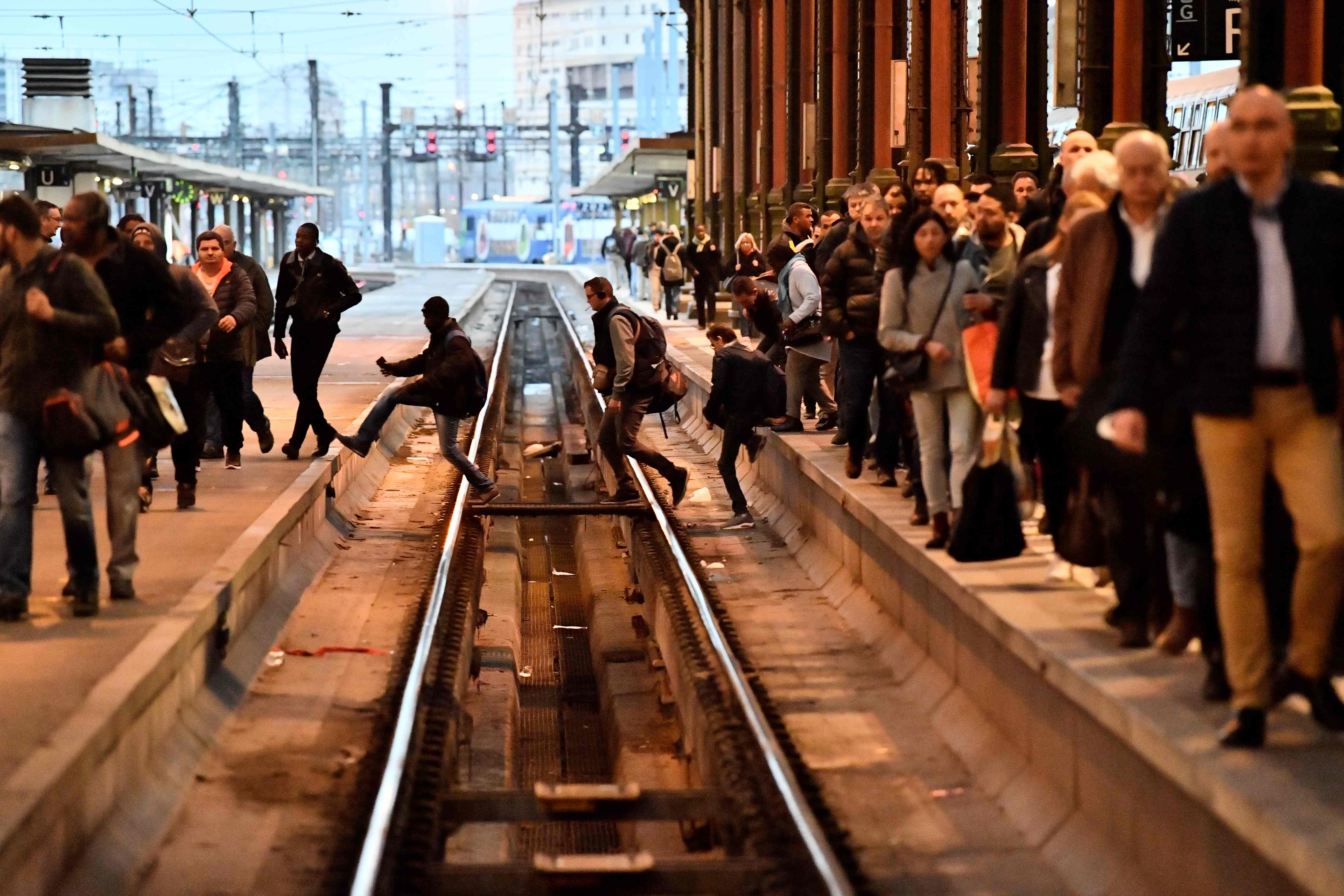 People cross railtracks in Gare de Lyon railway station in Paris on April 3, 2018, at the start of three months of rolling rail strikes.  Staff at state rail operator SNCF walked off the job at 7 pm on April 2, the first in a series of walkouts affect