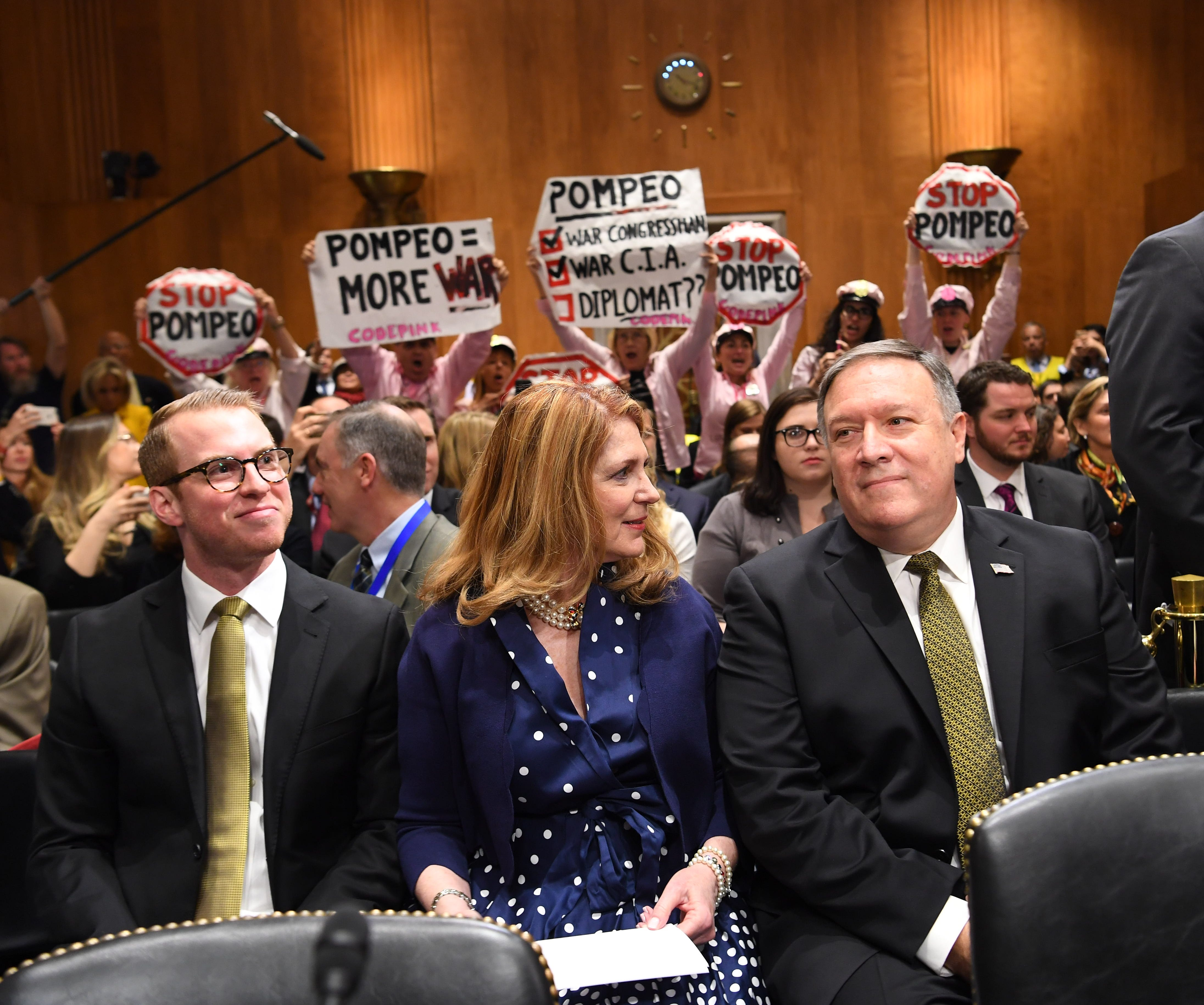 Protestors hold signs from the CODEPINK grassroots anti-war group in the back of the hearing room while Mike Pompeo (R) sits with his wife Susan Pompeo (C) before his scheduled testimony before the Senate Foreign Relations Committee during his confir