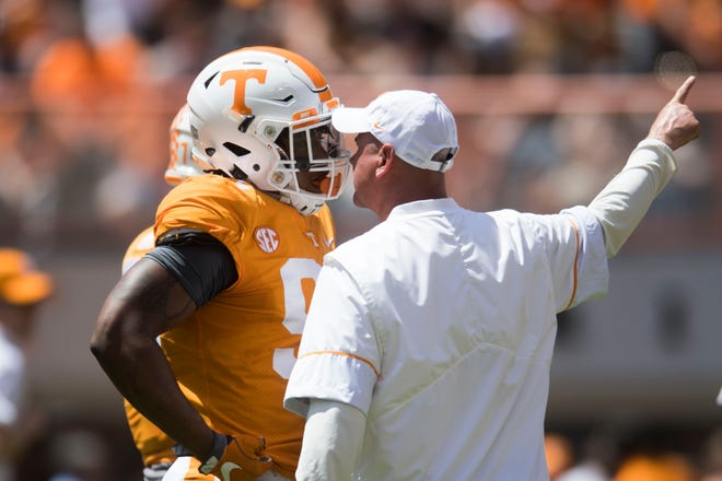 Tennessee coach Jeremy Pruitt speaks to running back Tim Jordan (9) before the Orange & White spring game on April 21.