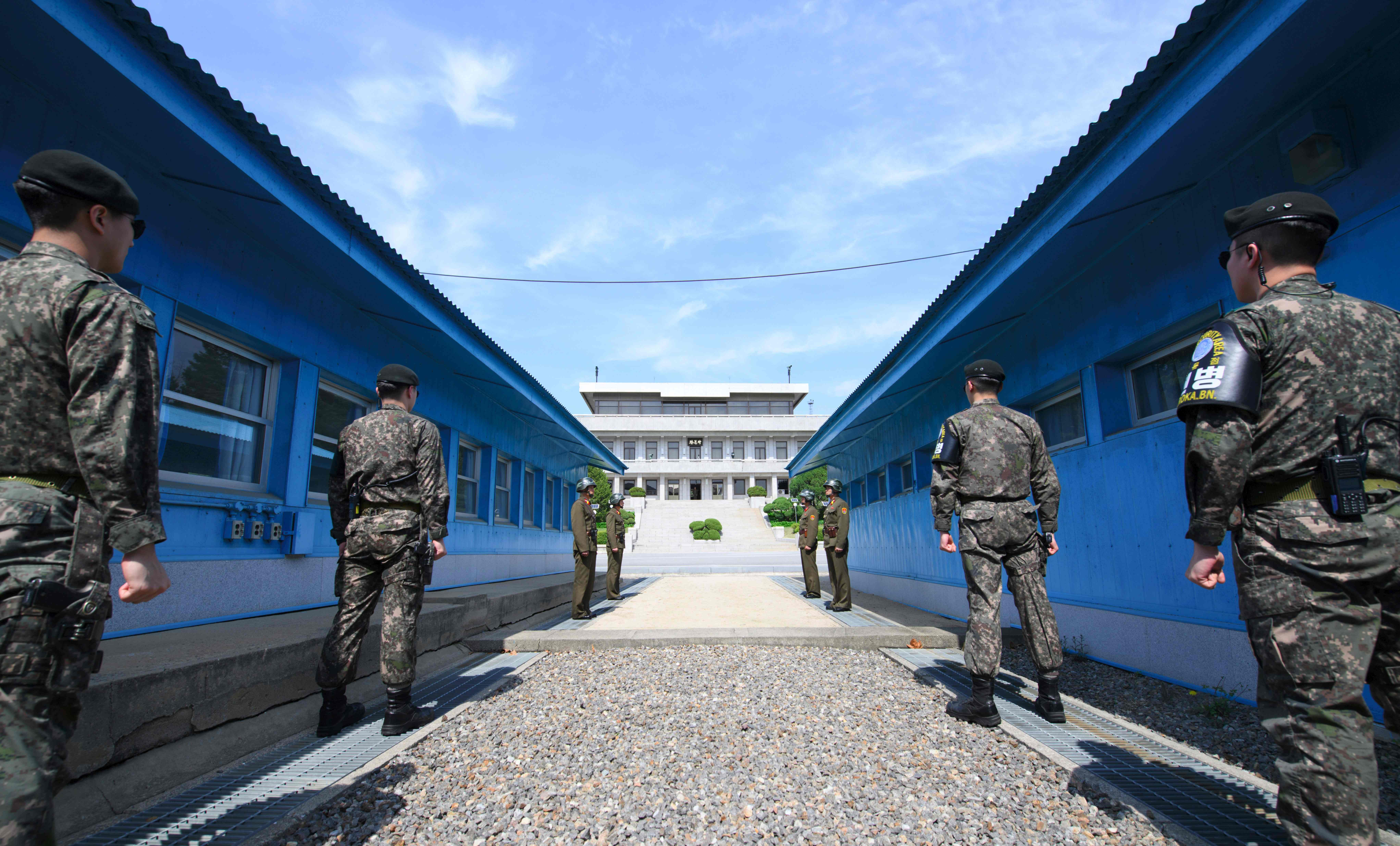 South Korean soldiers (front) and North Korean soldiers (rear) stand guard before the military demarcation line on the each side of the truce village of Panmunjom in the Demilitarized zone (DMZ) dividing the two Koreas on April 26, 2018 ahead of the