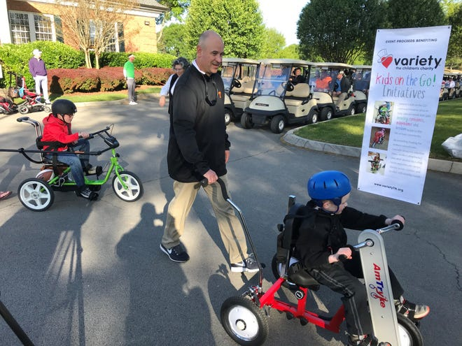 Tennessee football coach Jeremy Pruitt assists a child on a specially equipped bicycle at Variety of Eastern Tennessee's annual golf tournament on Monday, April 30, 2018.