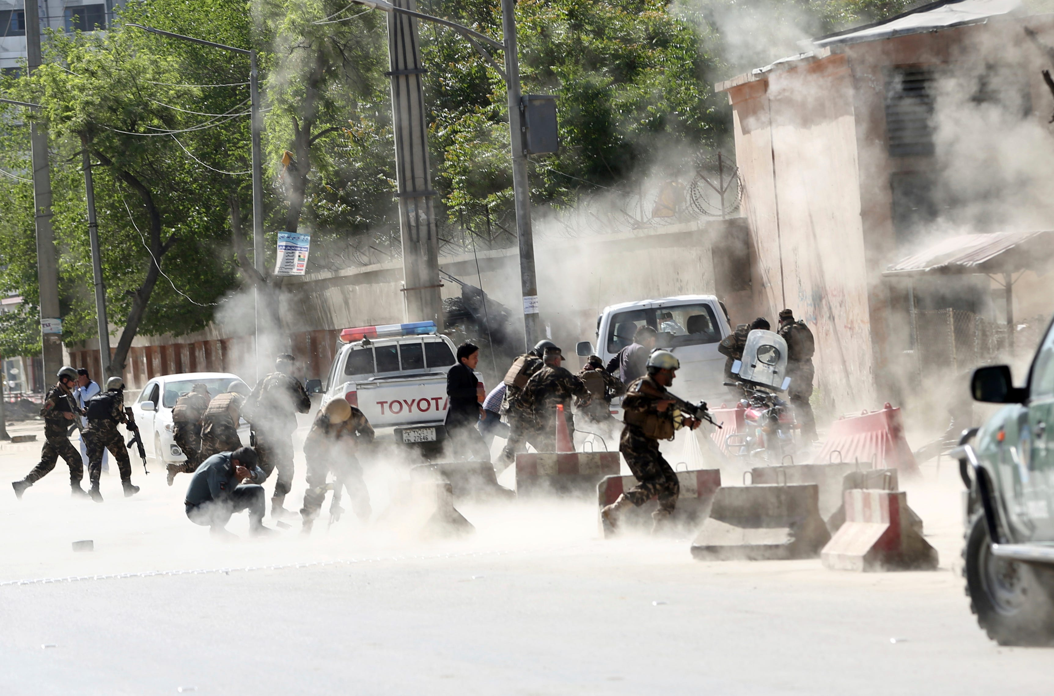 Security forces run from the site of a suicide attack after the second bombing in Kabul, Afghanistan, April 30, 2018. A coordinated double suicide bombing hit central Kabul on Monday morning,
