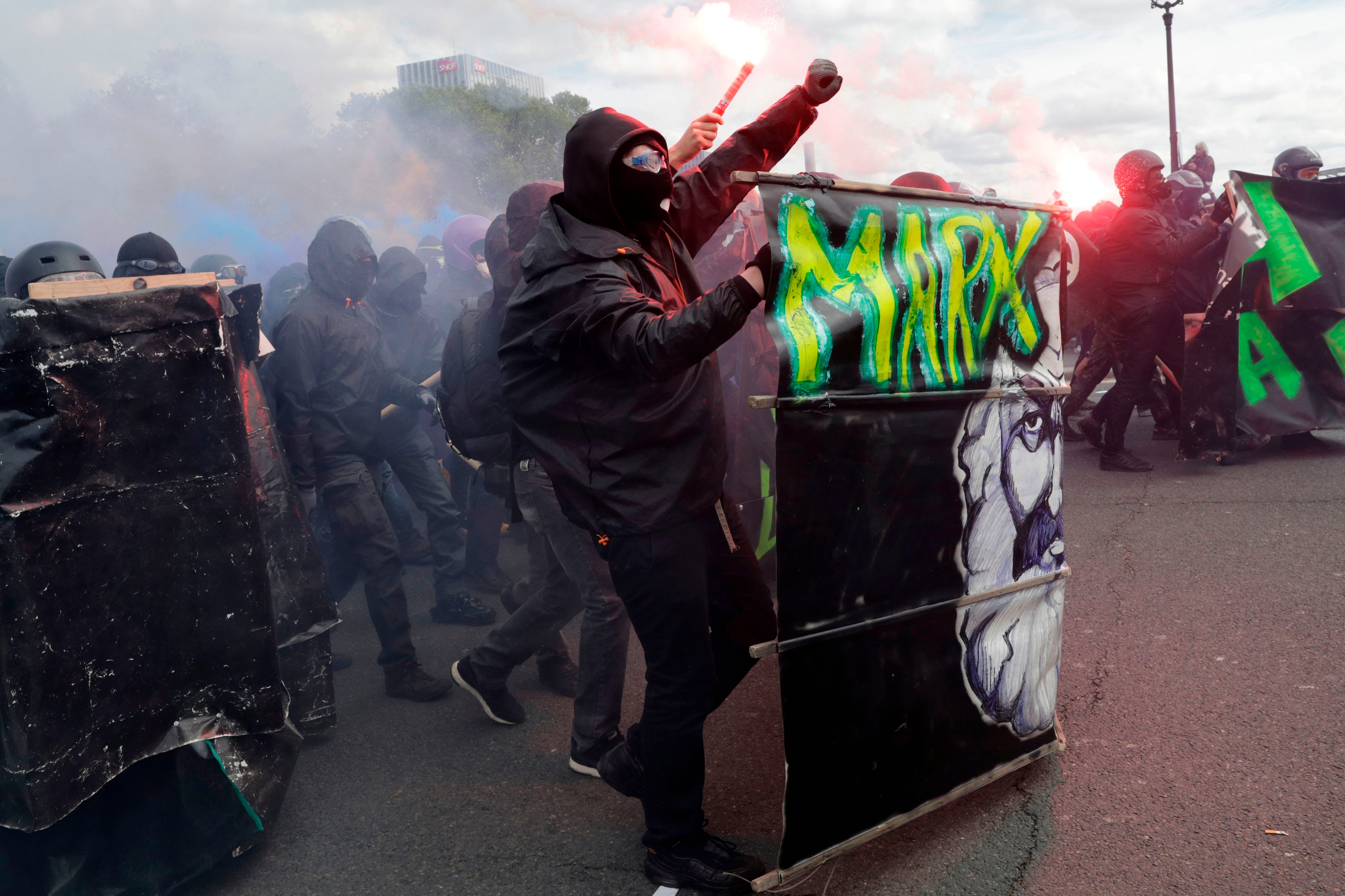Protestors dressed in black and with faces covered hold smoke bombs and gesture as they take part in a march for the annual May Day workers' rally, in Paris, on May 1, 2018.