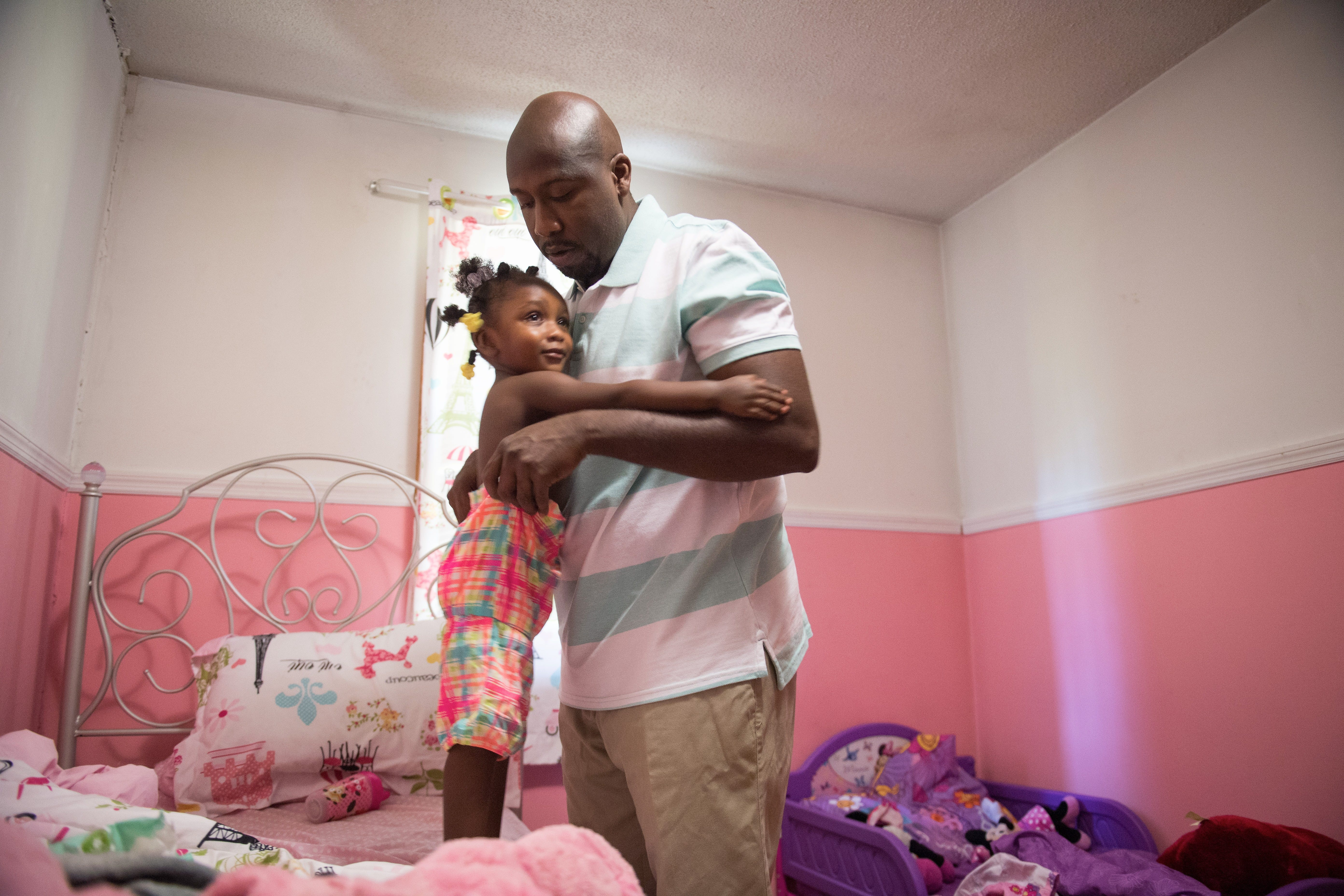 Marco Mention dresses his daughter Serenity at their home in Nesmith, South Carolina. He balances work as a school bus driver with the demands of raising three daughters alone.
