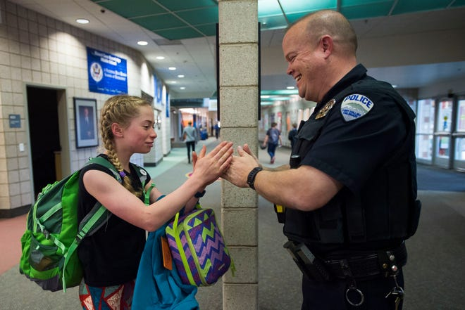 Fort Collins school resource officer Keith Maynard and seventh grader Liesel Smid exchange an elaborate choreographed handshake on Thursday, May 3, 2018, at Kinard Core Knowledge Middle School in Fort Collins, Colo.