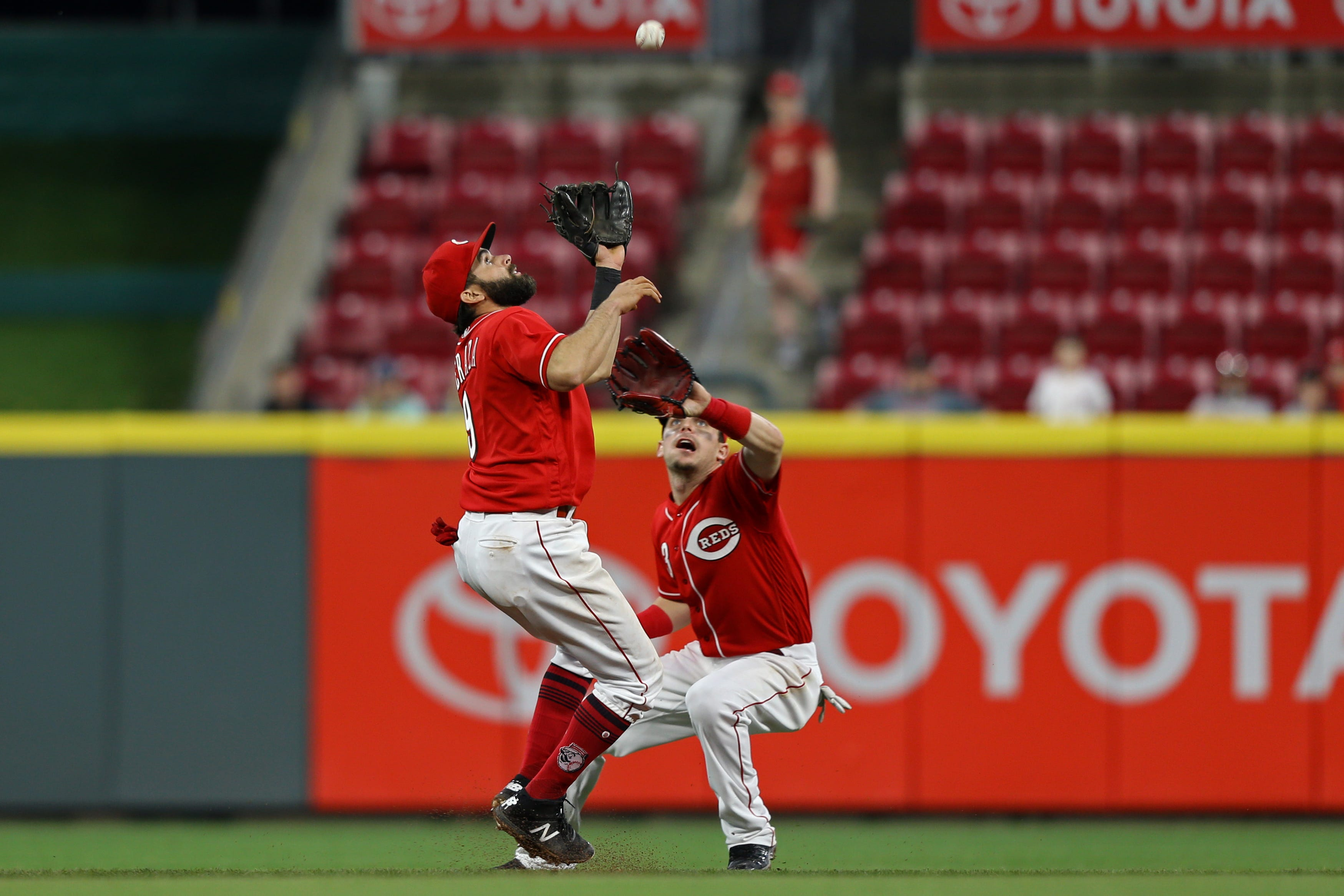 Cincinnati Reds second baseman Jose Peraza, left, and second baseman Scooter Gennett field a fly ball hit by Miami Marlins shortstop Yadiel Rivera during the ninth inning at Great American Ball Park.