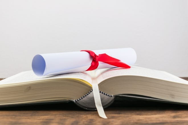 A parchment diploma scroll, rolled up with red ribbon on book on wood background