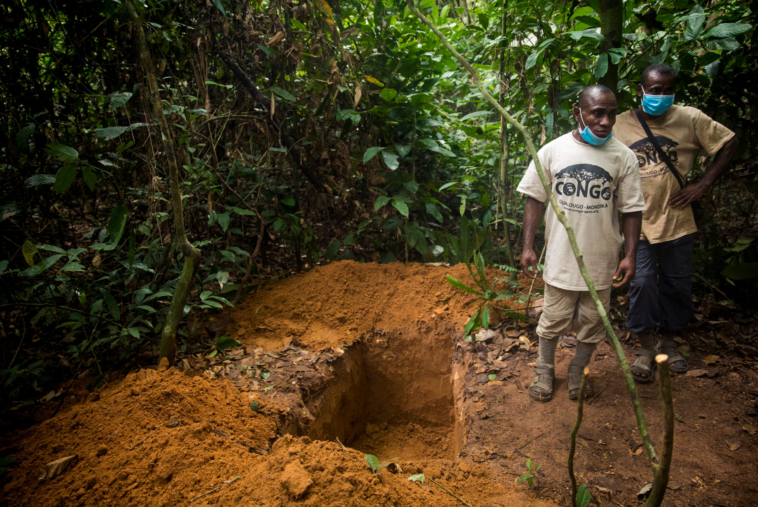 Etecko Lambert and Rene Ngoto stand by the grave they just dug for Etecko, a male gorilla, who died that morning after three weeks of losing weight and growing more and more lethargic. Etecko was named after the tracker standing next to his grave.