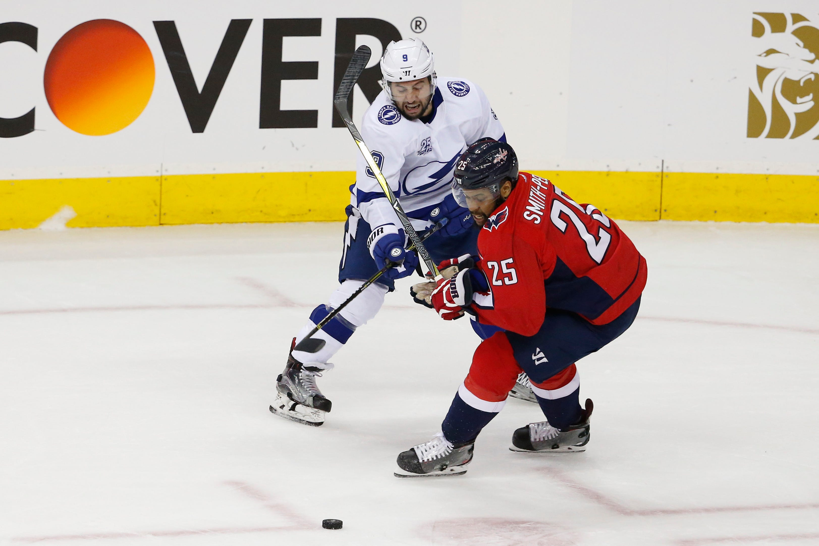 Tampa Bay Lightning center Tyler Johnson, left, passes the puck as Washington Capitals right wing Devante Smith-Pelly defends during the first period in game three of the Eastern Conference Final in the 2018 Stanley Cup Playoffs at Capital One Arena