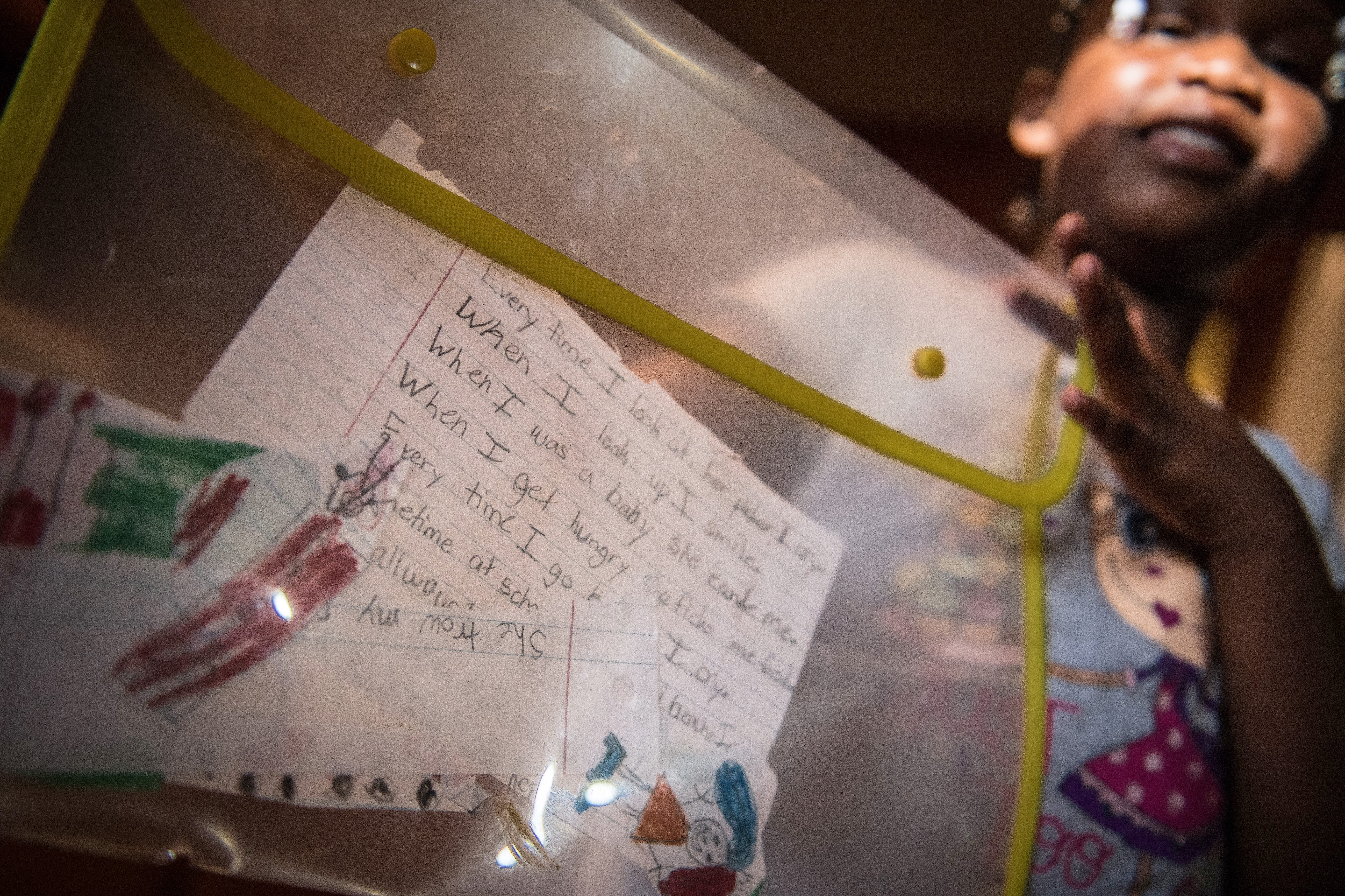 """""""When I look up, I smile,"""" Shekinah Mention wrote about her mother YoLanda. She holds up some of her writing and drawings about her mother's life that she has saved at her home in Nesmith, South Carolina."""