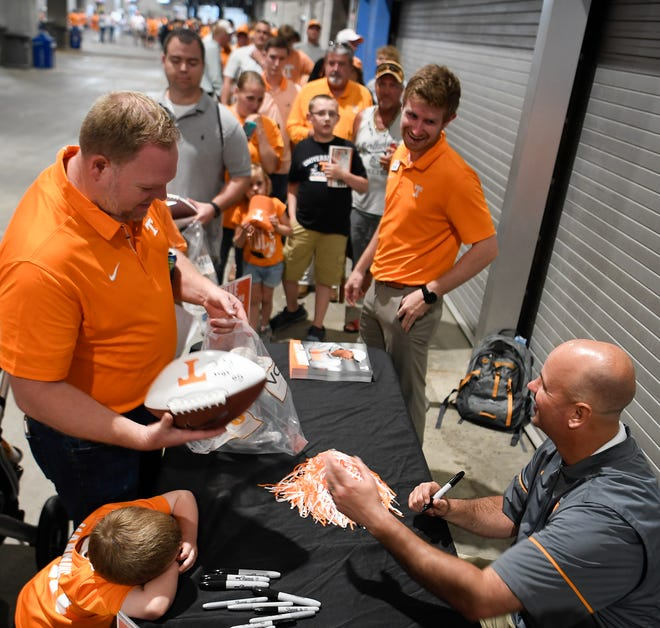 Vols football coach Jeremy Pruitt signs autographs for fans during the UT All-Sports Picnic on Thursday at Nissan Stadium.