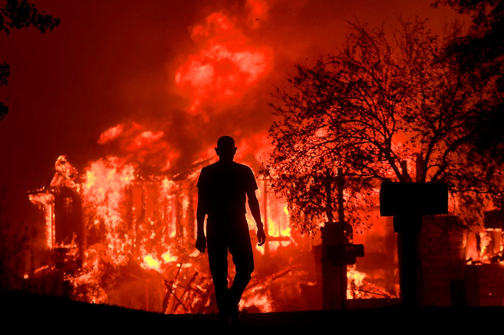 In this Oct. 9, 2017, file photo, Jim Stites watches part of his neighborhood burn in Fountaingrove. Police body-camera footage from 2017's wildfires in California's wine country shows officers running door-to-door urging people to flee and rescuing elderly residents of a retirement community as flames bear down. Video obtained by the San Jose Mercury News is from the point-of-view of police in Santa Rosa, as they sprint through swirling smoke amid the firestorm. (Kent Porter/The Press Democrat via AP, File)