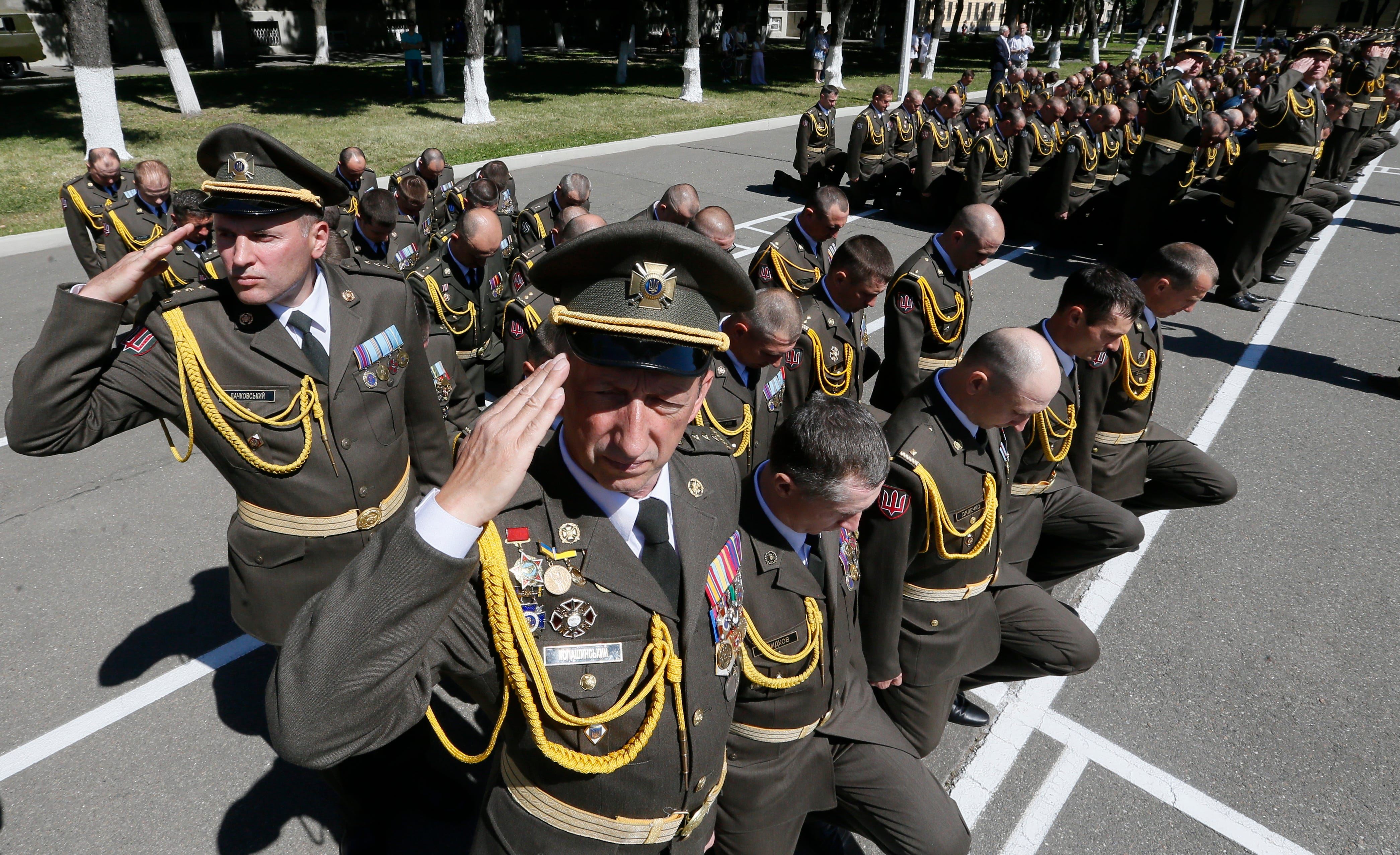 Ukrainian officers kneel in honor of their lost friends during the Graduation Day of the National Defense University, in Kiev, Ukraine. About 500 officers received their diplomas.