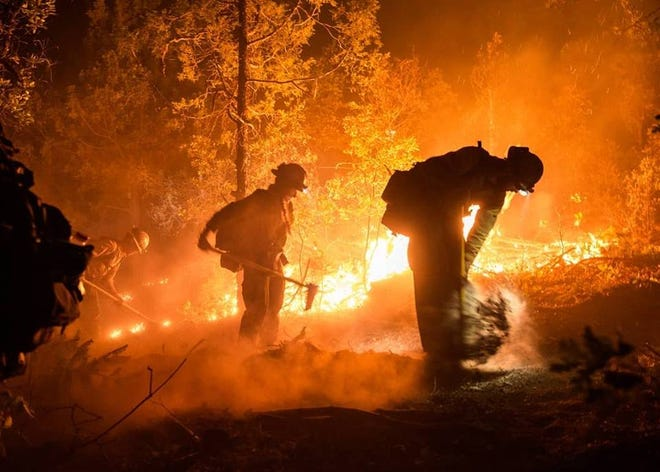 Firefighters from the Los Pinos Fire Protection District of Ignacio, Colorado, battle 416 Fire flames over the weekend in this undated photo provided by the San Juan National Forest.
