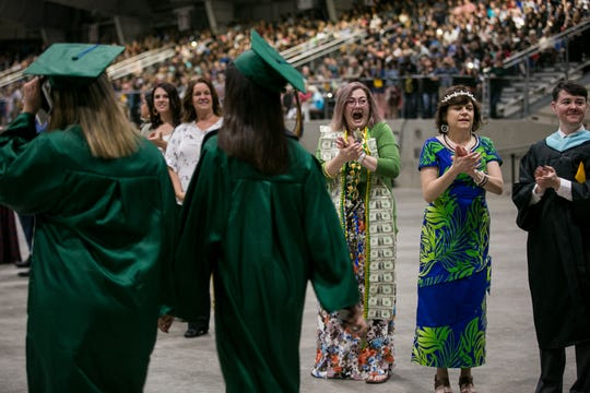Jillian Carey, an English and special education teacher at McKay High School, cheers for graduates as they enter their commencement at the Oregon State Fairgrounds Pavilion in Salem on Friday, June 8, 2018.