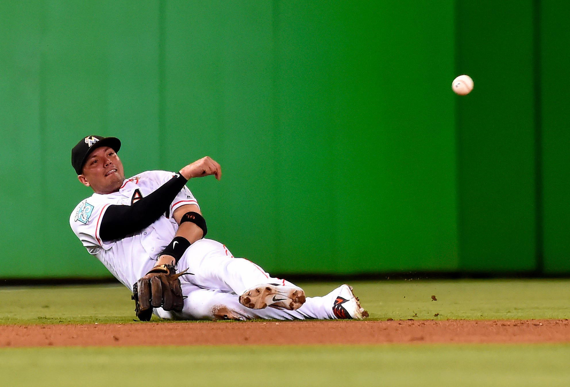 Miami Marlins shortstop Miguel Rojas attempts to throw to second base in the fourth inning against the San Francisco Giants at Marlins Park in Miami.
