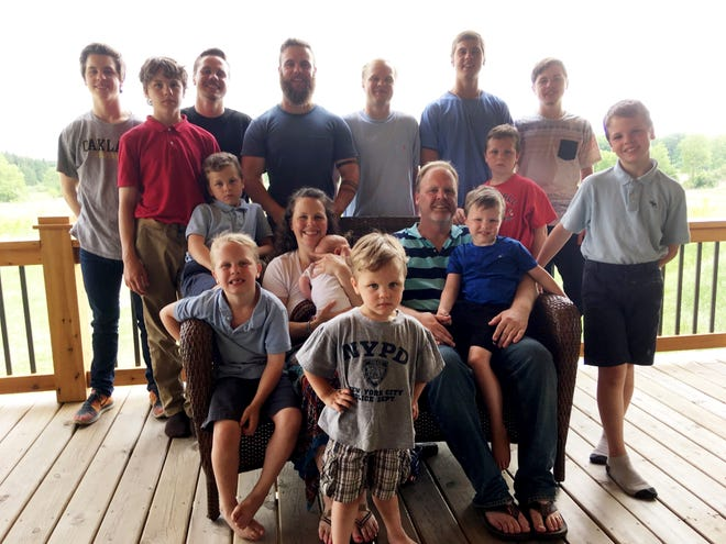 In a photo from May 30, 2018, the Schwandt family poses for a photo at their farm in Lakeview, Mich. Standing from left are Tommy, Calvin, Drew, Tyler, Zach, Brandon, Gabe, Vinny and Wesley. Seated, starting at upper left are Charlie, Luke, mother Kateri holding Finley, father Jay with Tucker and Francisco in the foreground. The 14-boy family ranges in age from 2 months to 25 years. And no girls.