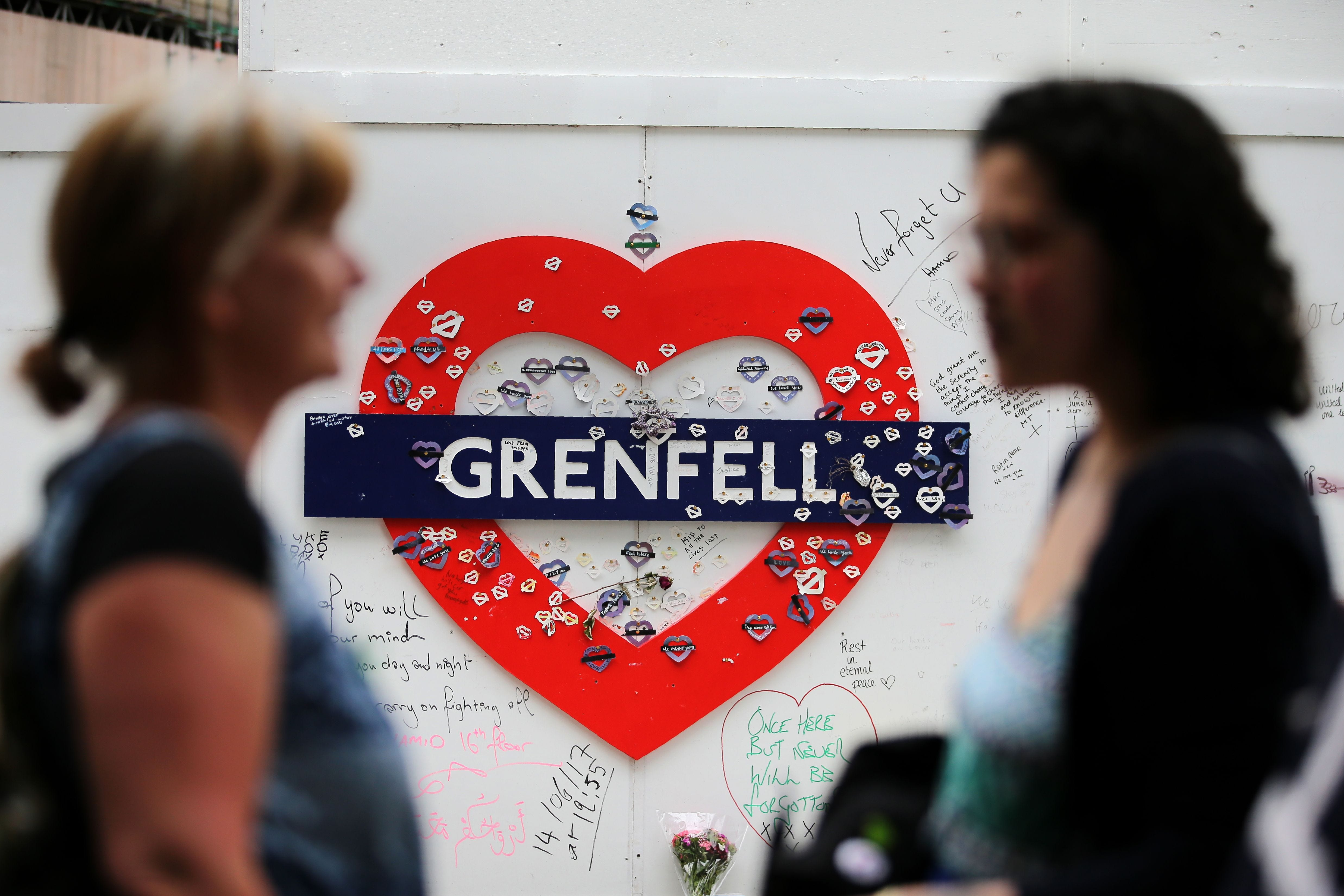 Messages of condolence for the victims of the Grenfell Tower fire are pictured on a fence near to the burned-out shell of Grenfell Tower block in west London on June 13, 2018.  Commemorations begin on June 13, 2018, to honour the 71 people who died wh