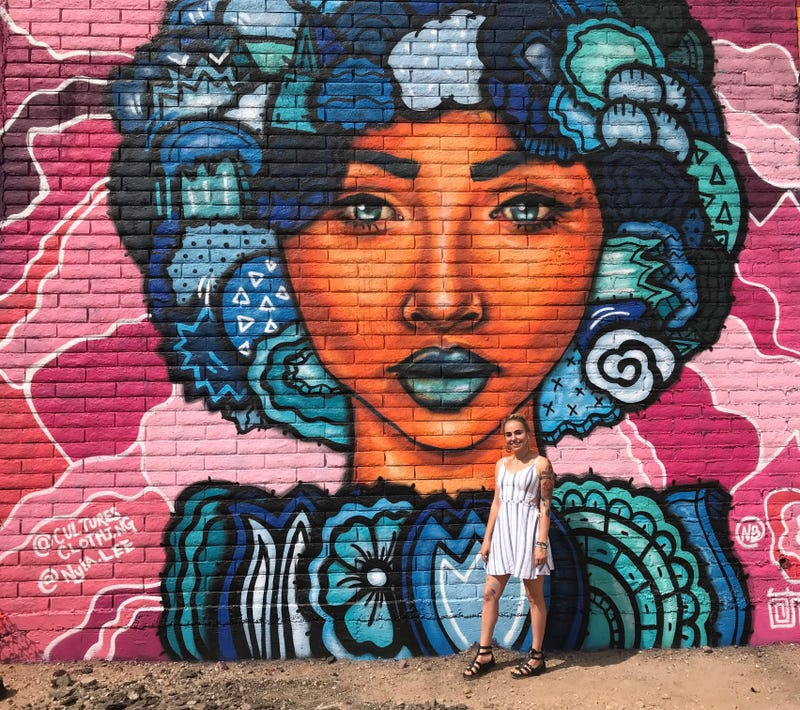 Street artist Nyla Lee stands by a mural she painted on Seventh Street in Phoenix.