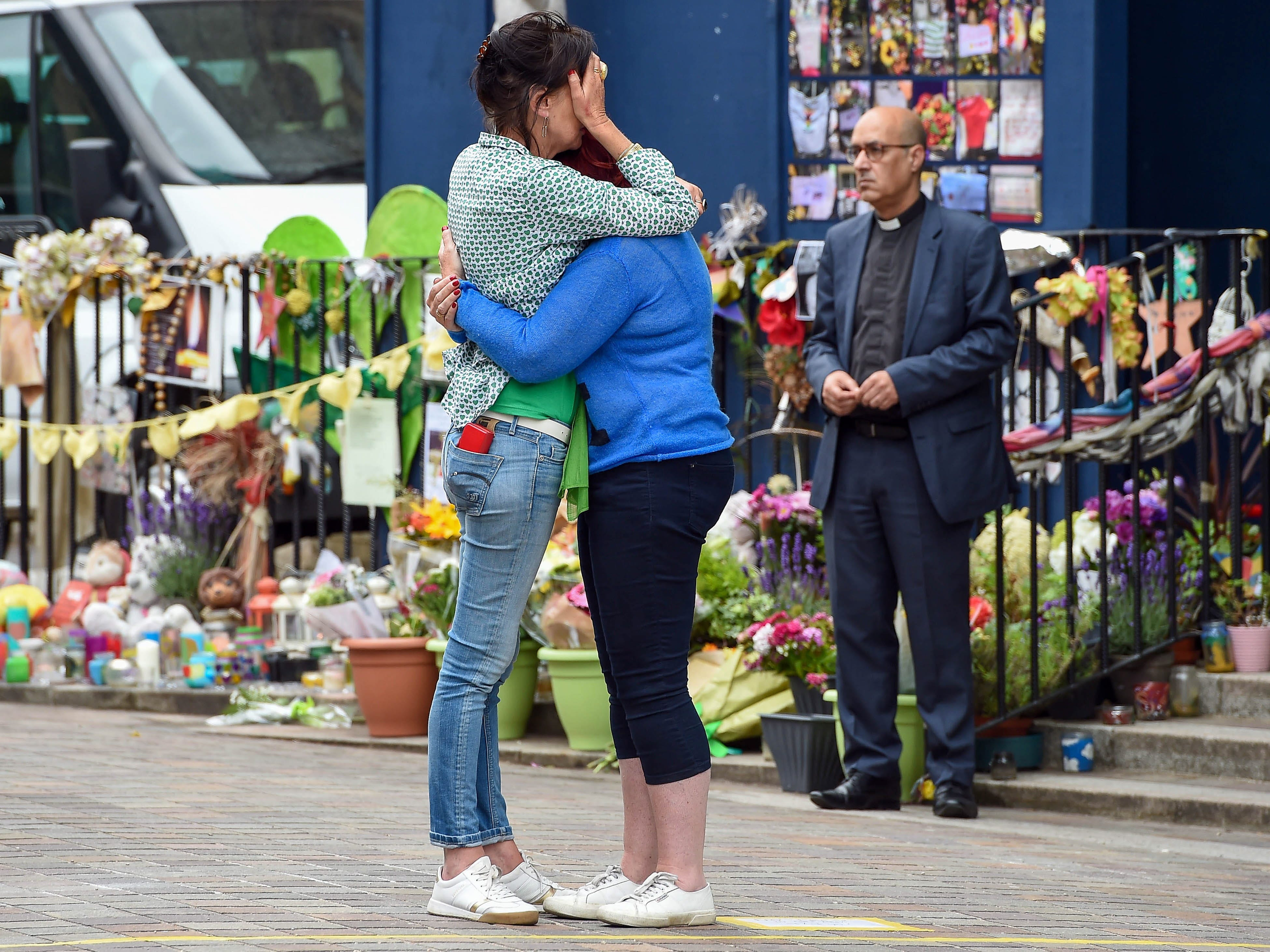 Two women comfort each other outside Notting Hill Methodist church, on the first anniversary of the Grenfell Tower fire in London, June 14, 2018. The fire devastated the 24-story North Kensington tower block on June 14, 2017 killing 72 residents.