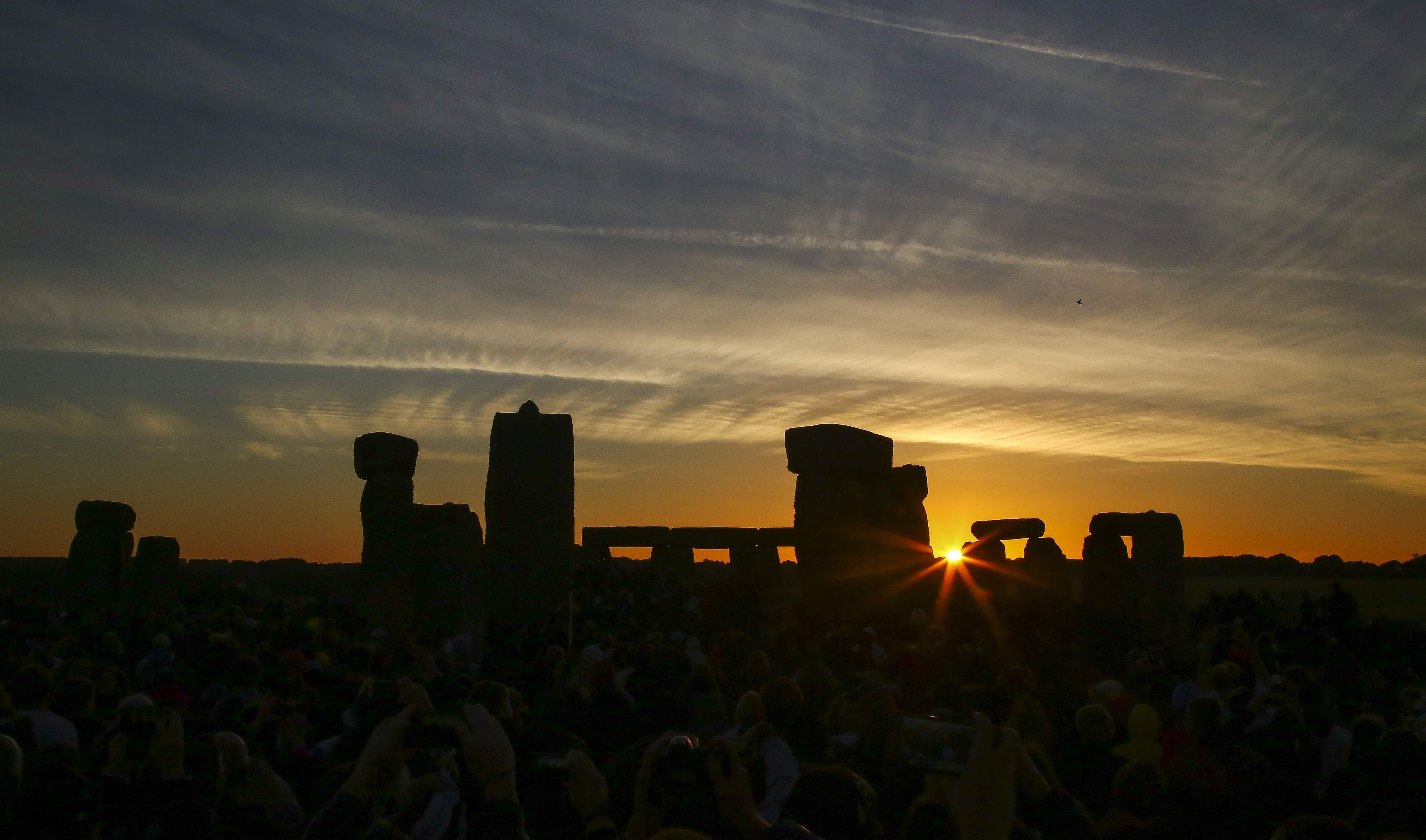 Revellers watch the sunrise as they celebrate the pagan festival of Summer Solstice at Stonehenge in Wiltshire,  England on June 21, 2018.  The festival, which dates back thousands of years, celebrates the longest day of the year when the sun is at it